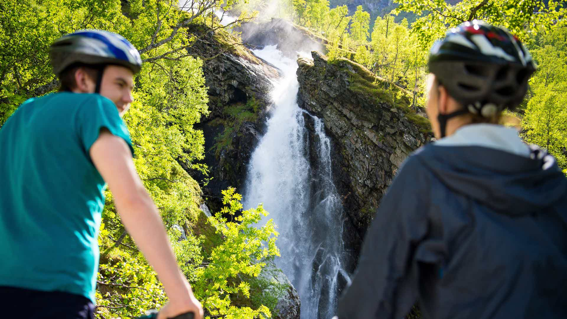 Two people wearing bike helmets and looking towards a waterfall in Flåmsdalen