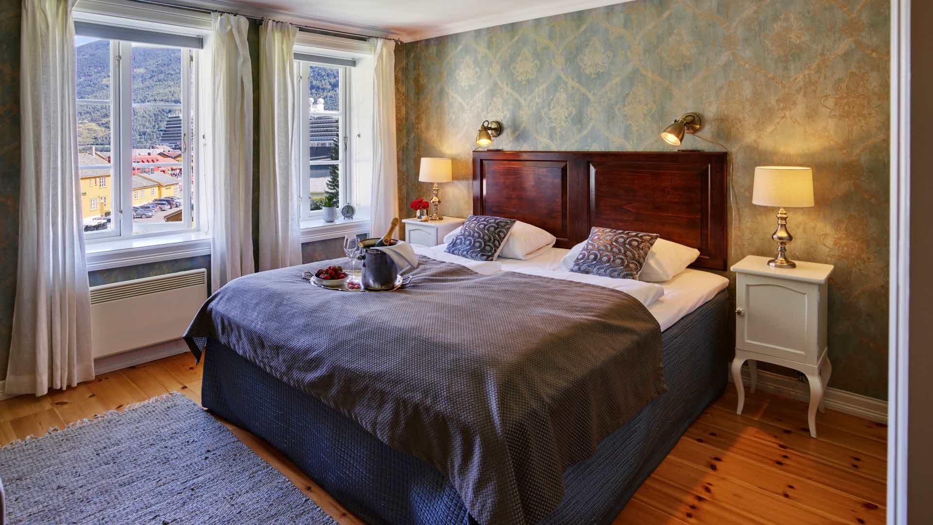 Historisk hotellrom med antikkinspirert grønn tapet, vindu med utsikt mot Flåm og dobbeltseng med et brett med champagne og jordbær på.