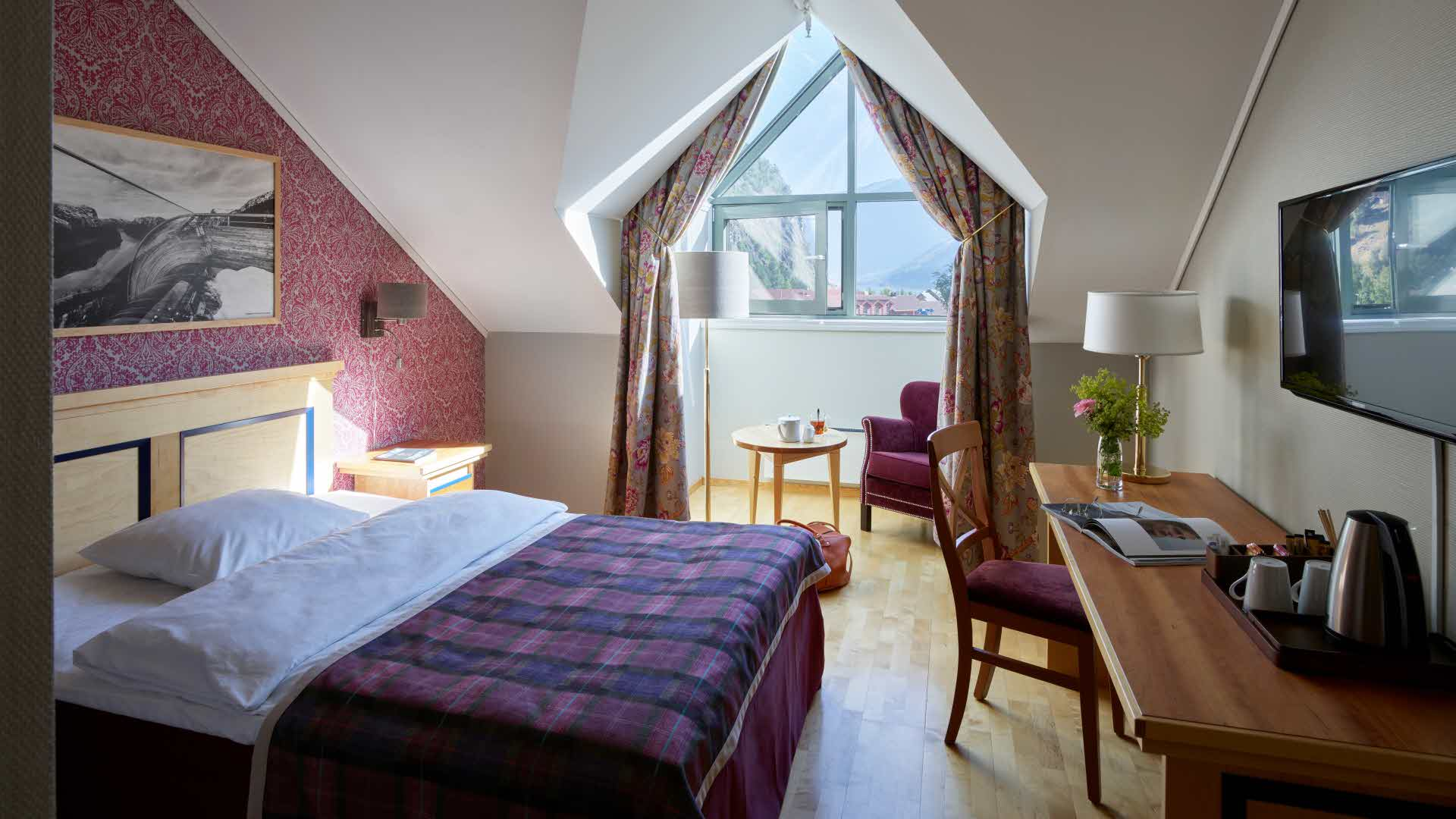 Single room at Fretheim with a queen size bed and desk in front and a chair and table in a bay window in the back.