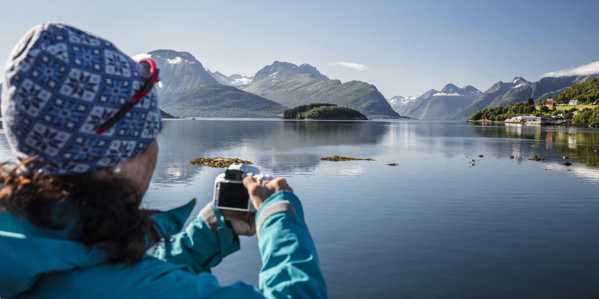 Una mujer haciendo una foto a bordo del crucero por el precioso fiordo de Hjørundfjord