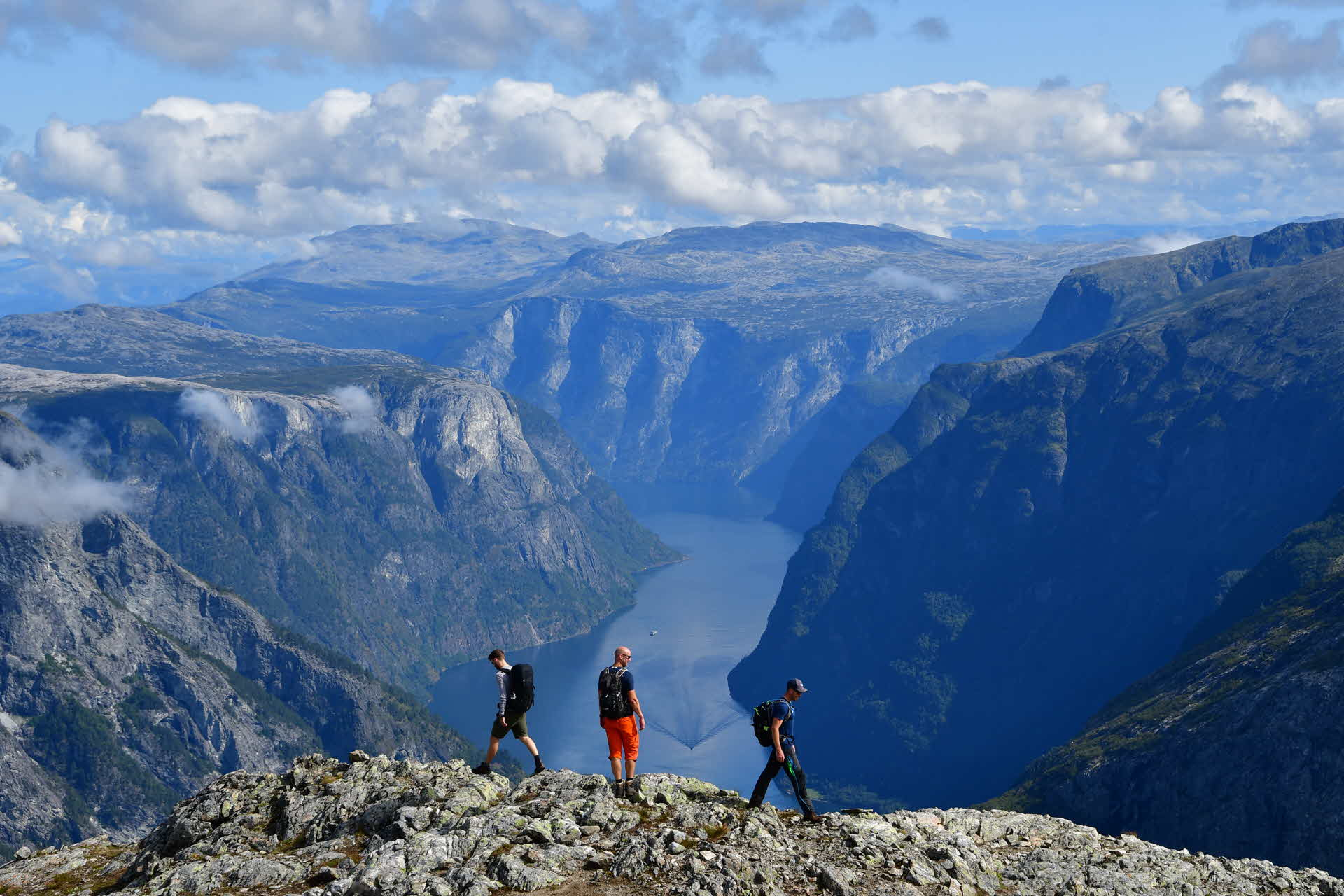 Three people standing on the edge of Bakkanosi, looking down towards the Nærøyfjord