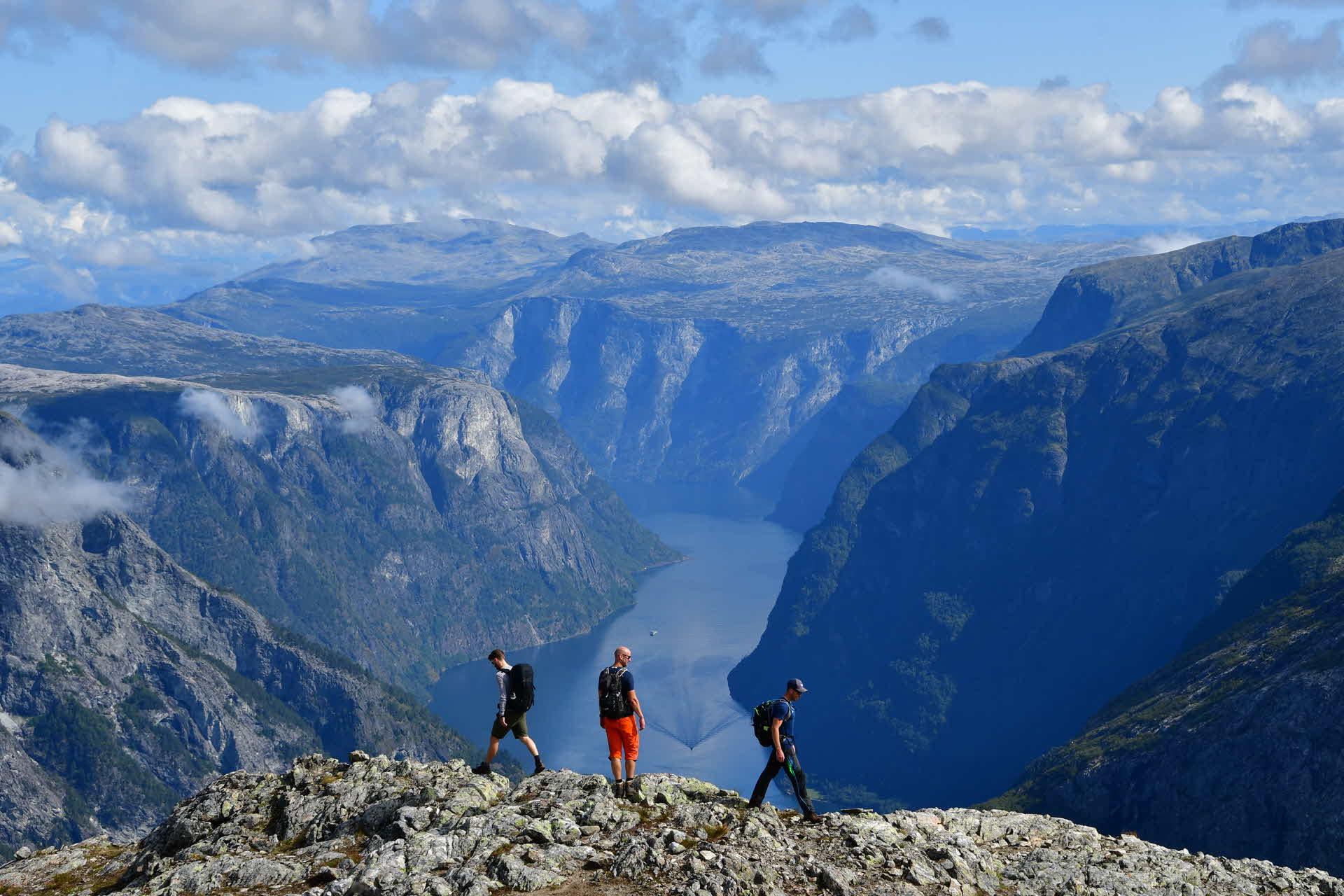 Три человека стоят на краю Бакканоси и смотрят вниз, в сторону Нерёй-фьорда
