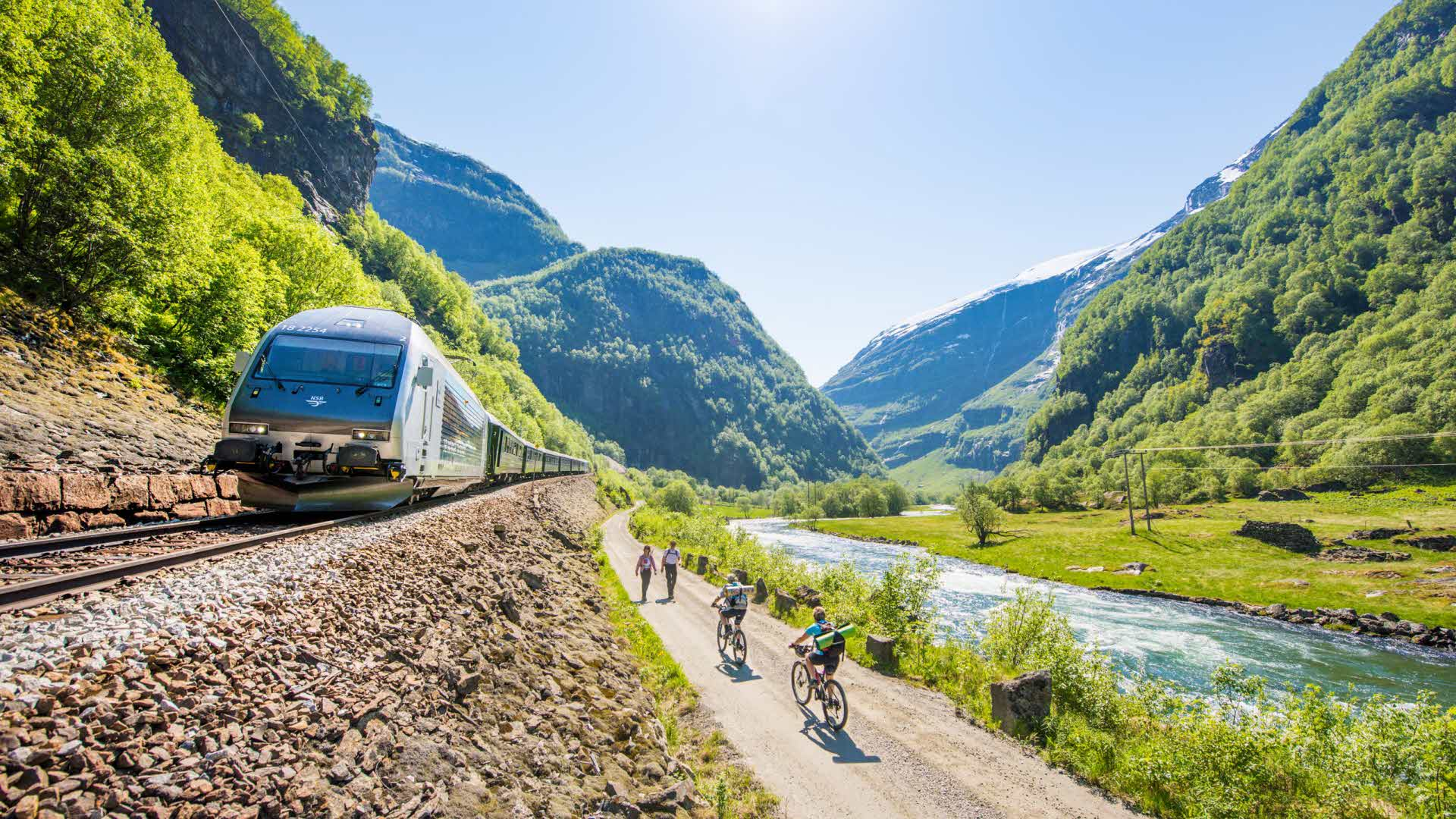 Pedestrians and cyclists travelling along the Flåmselv river on a warm summer day as the Flåm Railway passes by