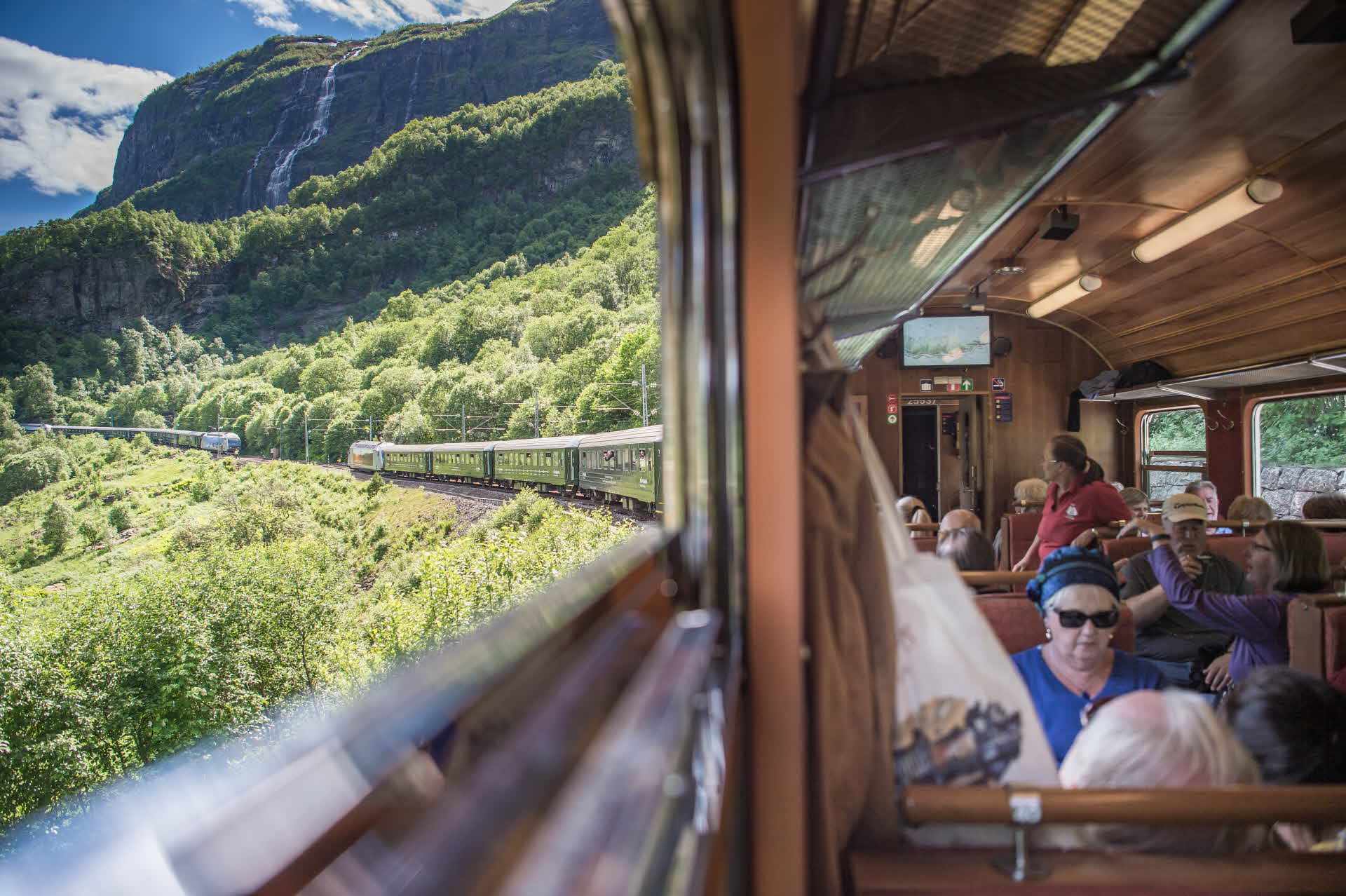 A view towards the Flåmsdalen Valley and an oncoming train from a window on the Flåm Railway