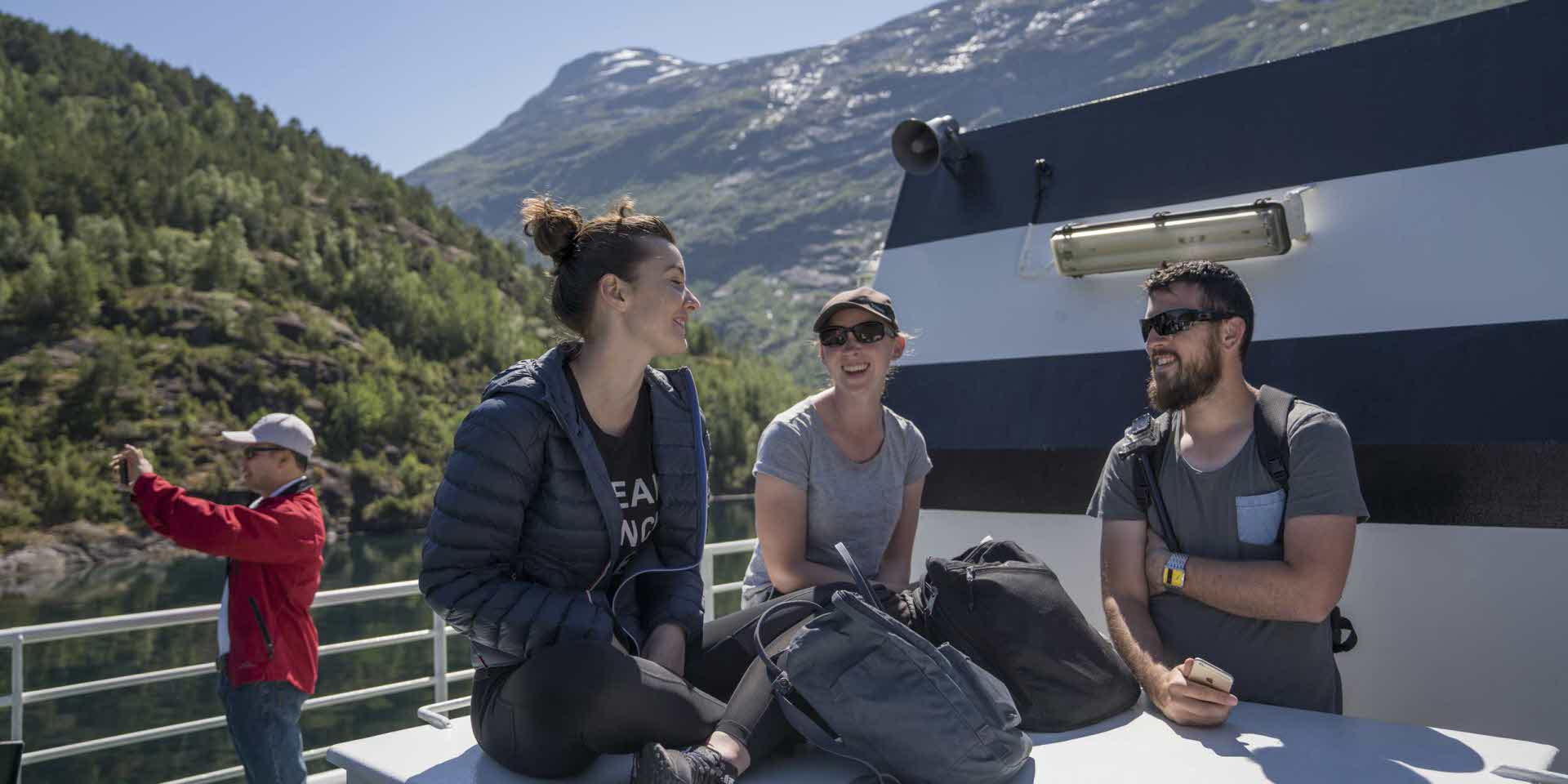 A group of tourists on a ferry deck in the Geirangerfjord