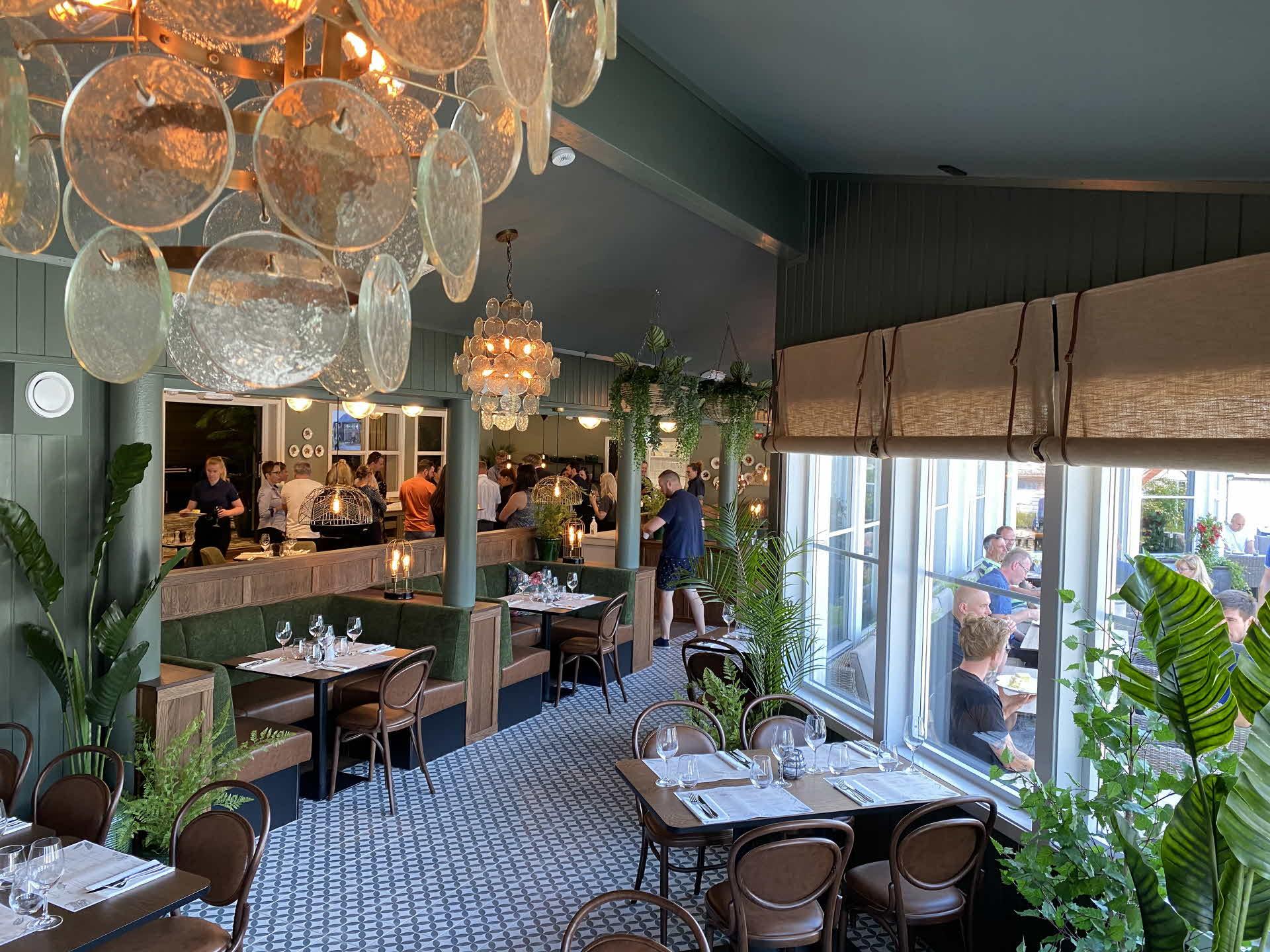 Bilde fra innsiden av botique-style restauranten i Hotel Aurlandsfjord hvor man ser folk hygger seg inne og ute på terrassen