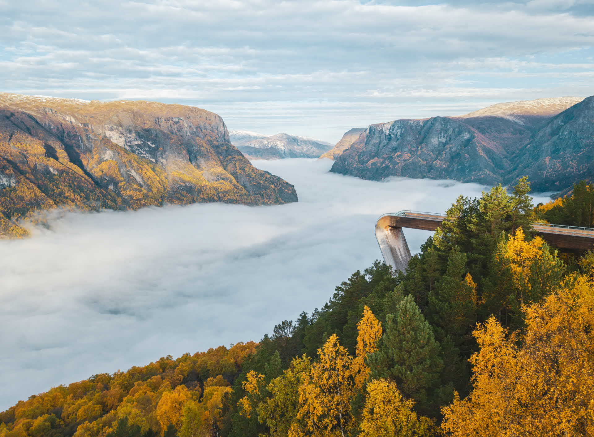 Kvinne står ved rekkverket på Stegastein utsiktspunkt og ser utover Aurlandsfjorden ein solrik dag