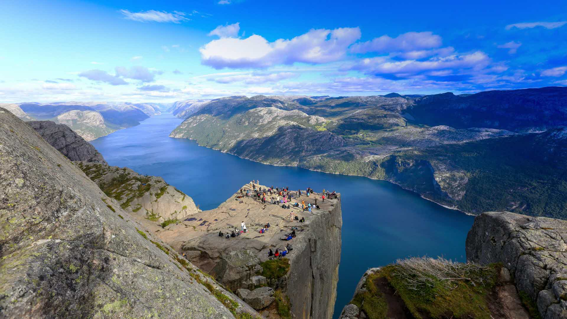 Panorama view from above Pulpit Rock, crowd of people standing near edge. Lysefjord can be seen as stretching out to infinity