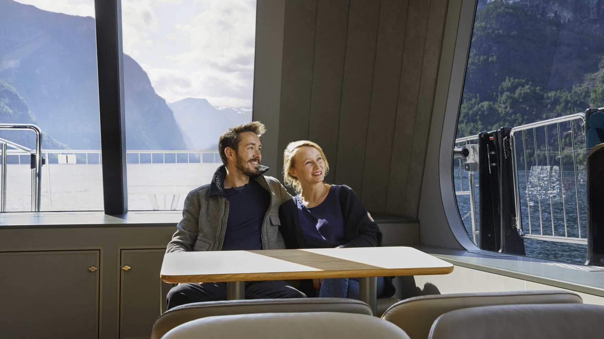 Couple in mid-20's enjoying the view from panorama windows on board Vision of The Fjords as sailing the Naeroyfjord