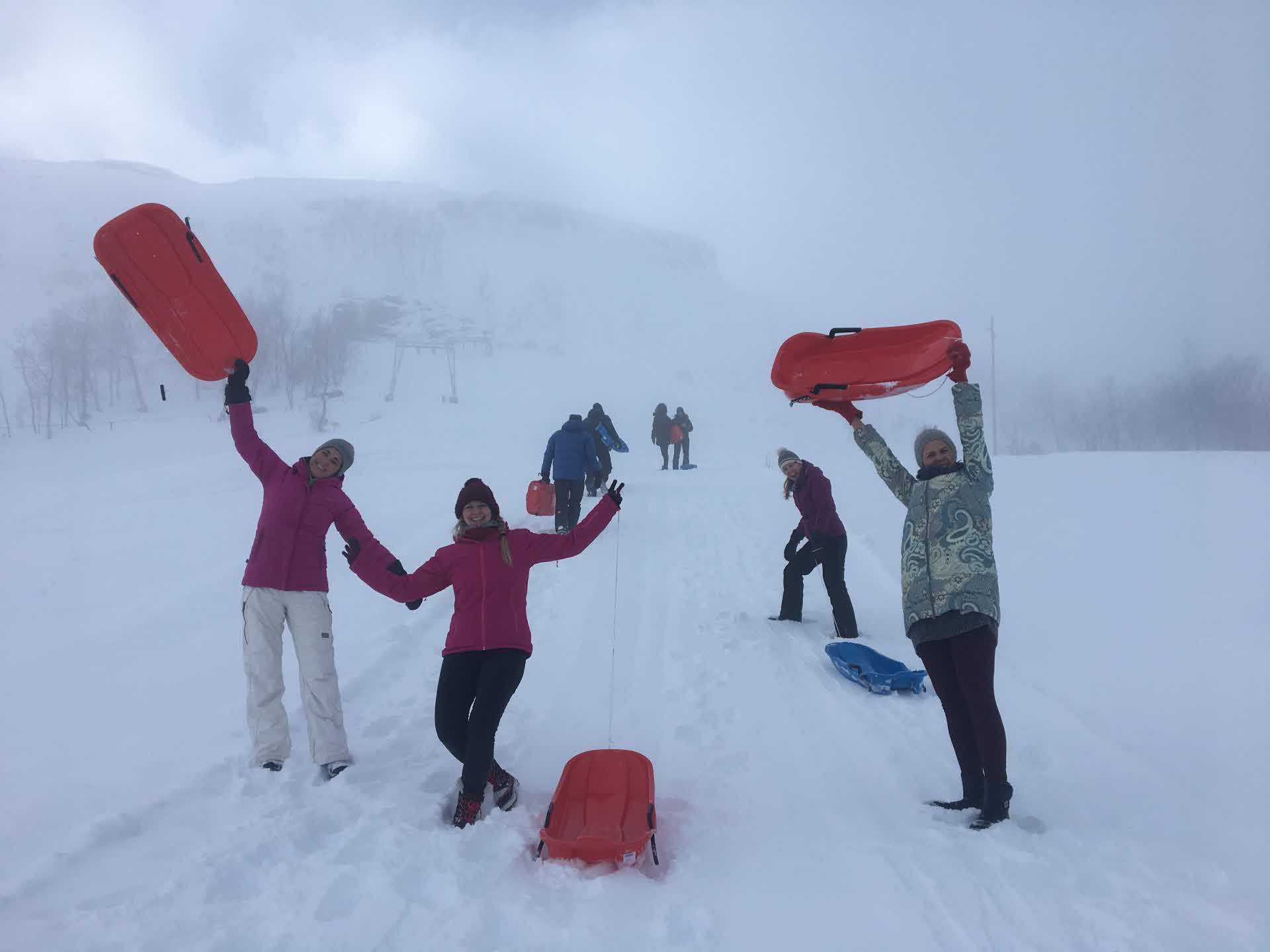 Group of people holding their snow sledges above their head, smiling as mist is covers the snow hill
