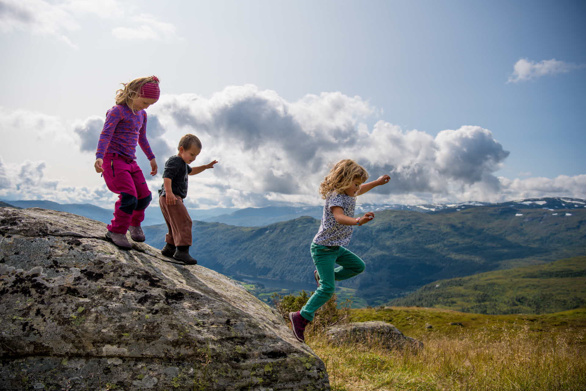 Three children jumping on a rock at the mountain in Myrkdalen