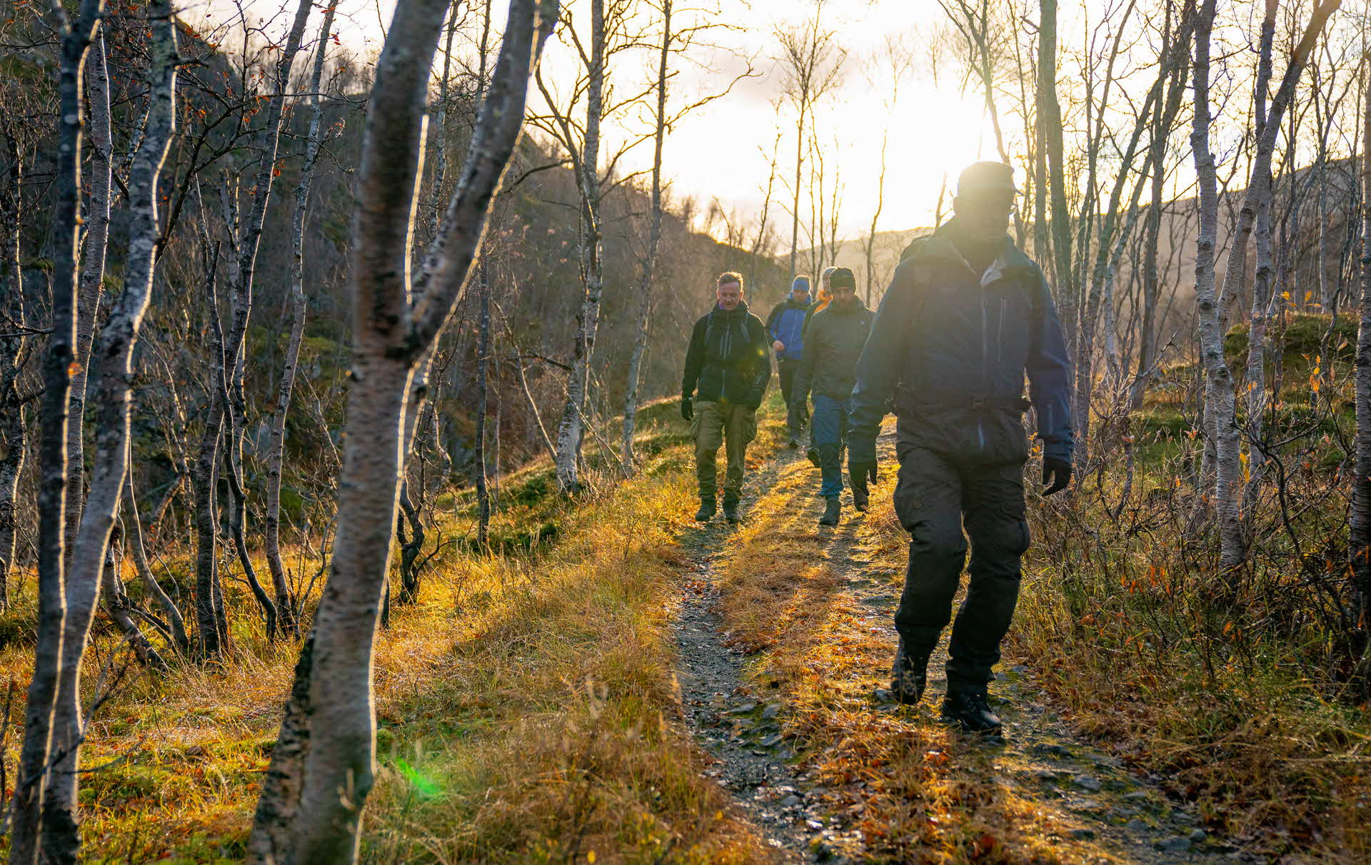 A group of men walking on Rallarveien on a sunny late autumn day
