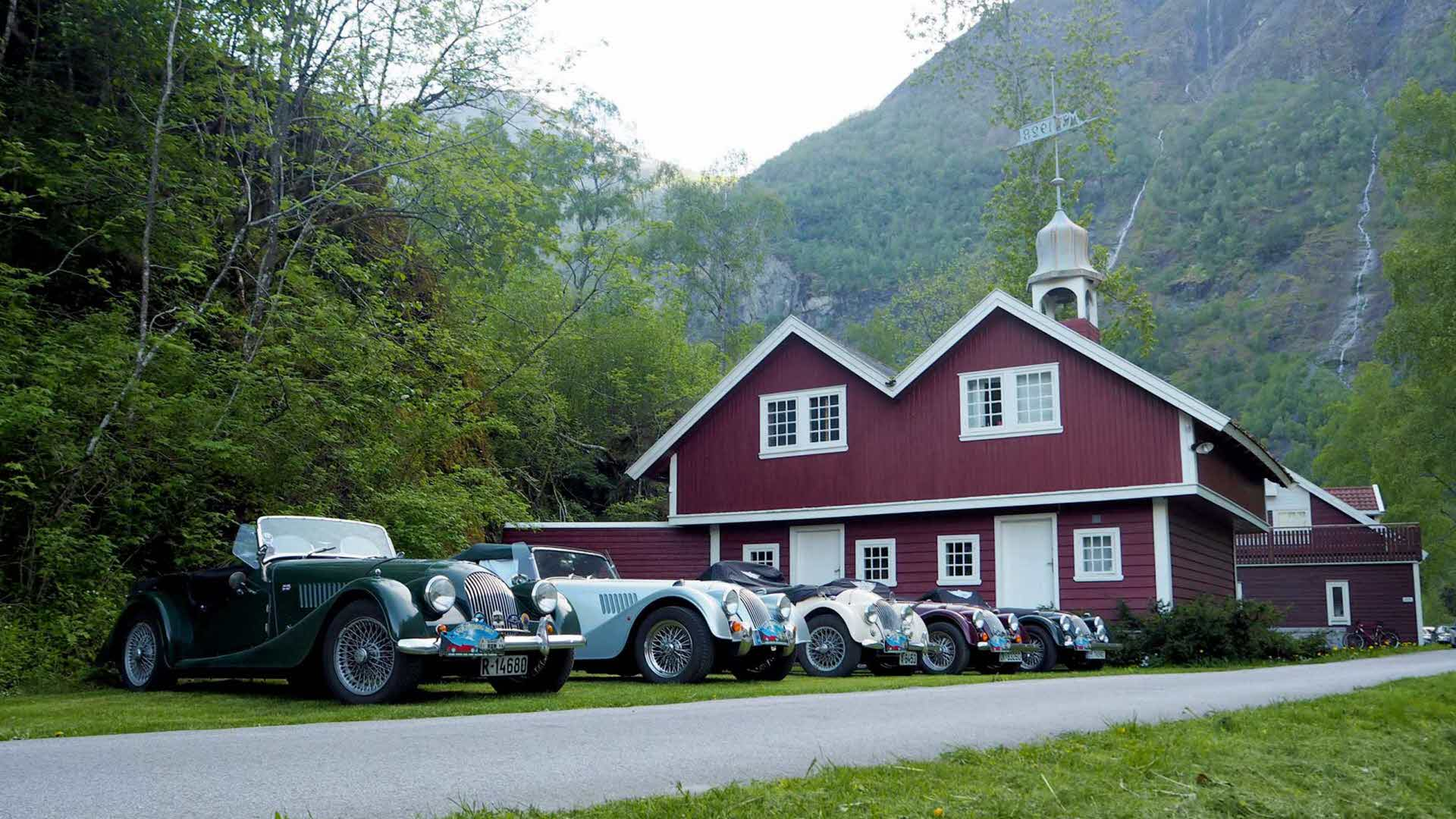 Five vintage sports cars parked outside the Storehouse in Flåm
