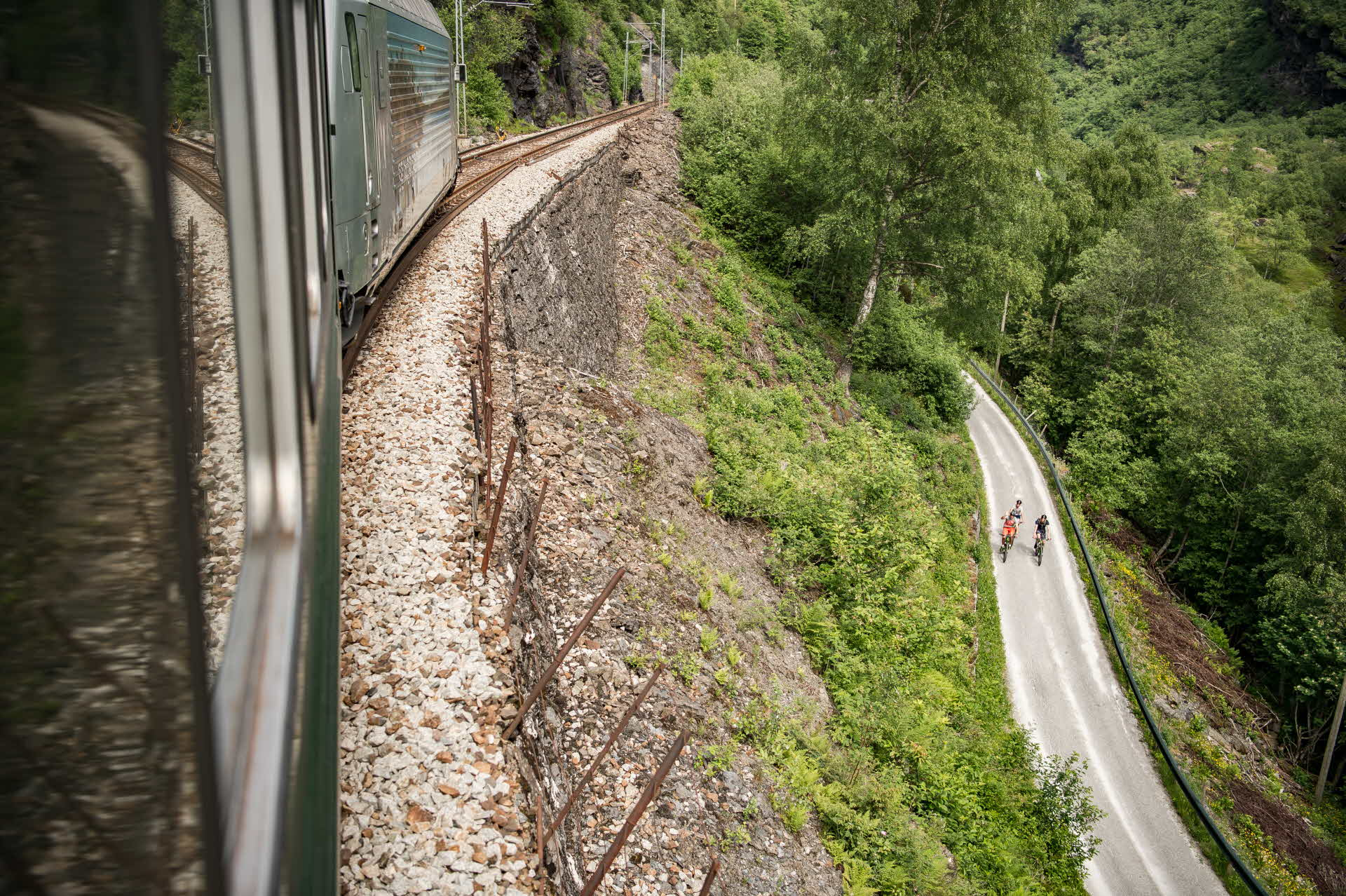 The side of Flåm Railway viewed from a train window and two cyclists on Rallarvegen below