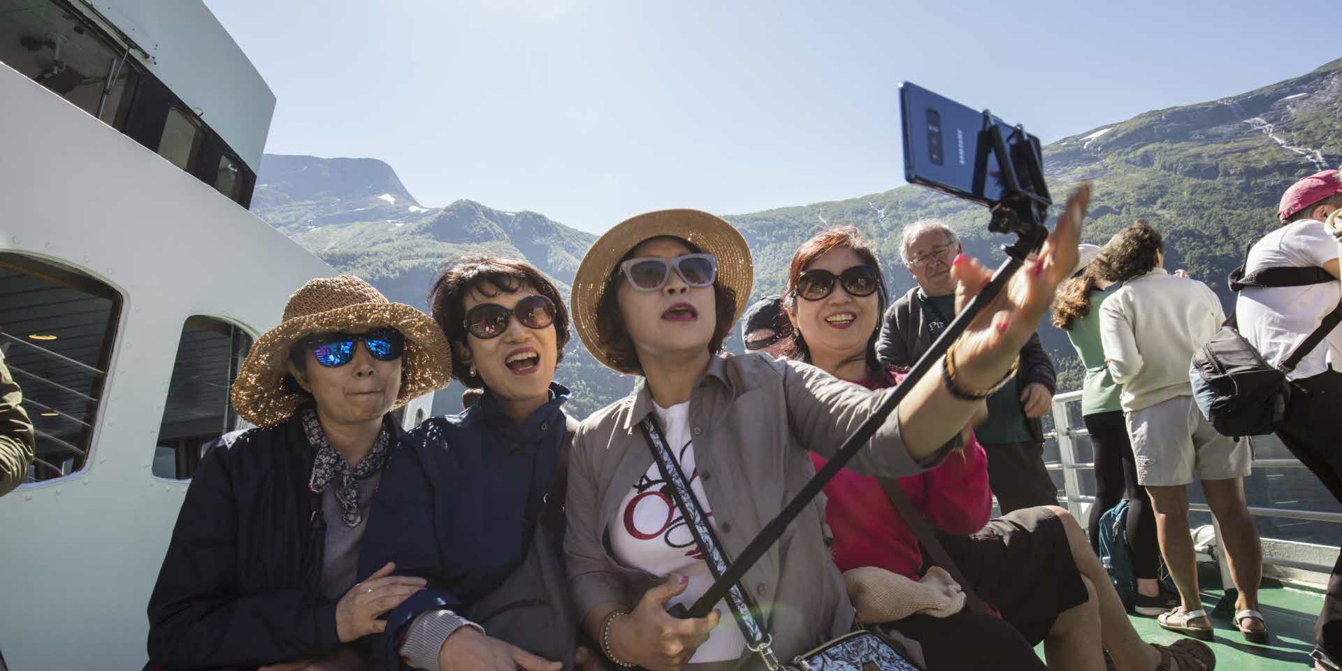 Four women taking a selfie on a ferry in Geiranger