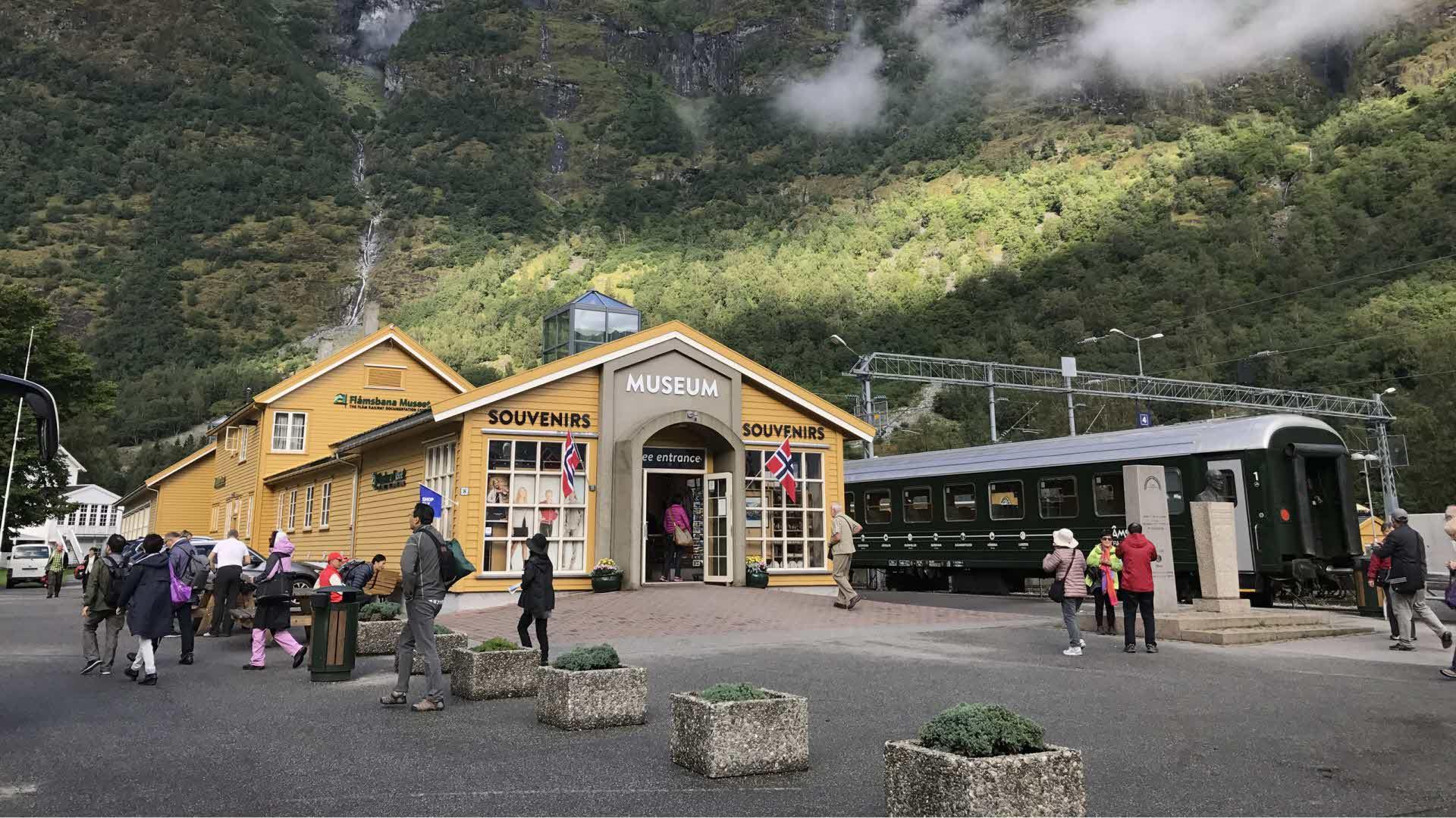Inngang Flåmsbanamuseet med et gammelt togsett parkert utenfor, høye fjell i bakgrunnen. Folk tar bilder og koser seg.