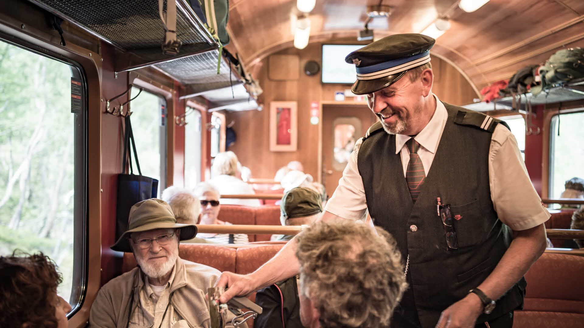 A conductor checks tickets on the Flåm Railway