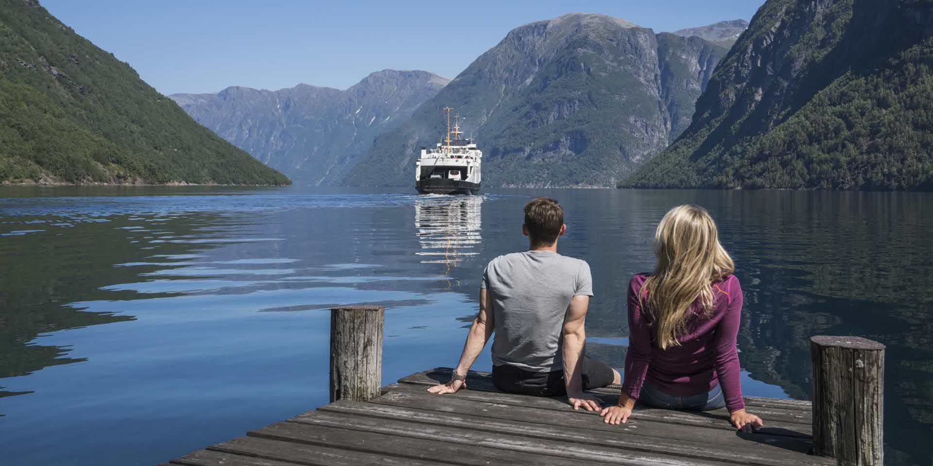 A woman and a man sitting on a wharf by the Geirangerfjord watching a ferry sailing