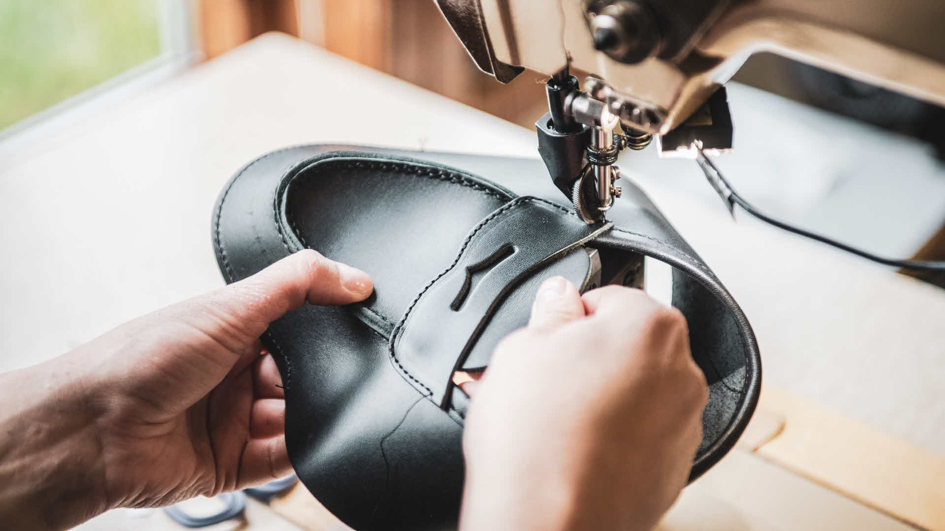 The top part of black leather Aurland shoe is being carefully stitched by worker as daylight reveal the curves of the hide