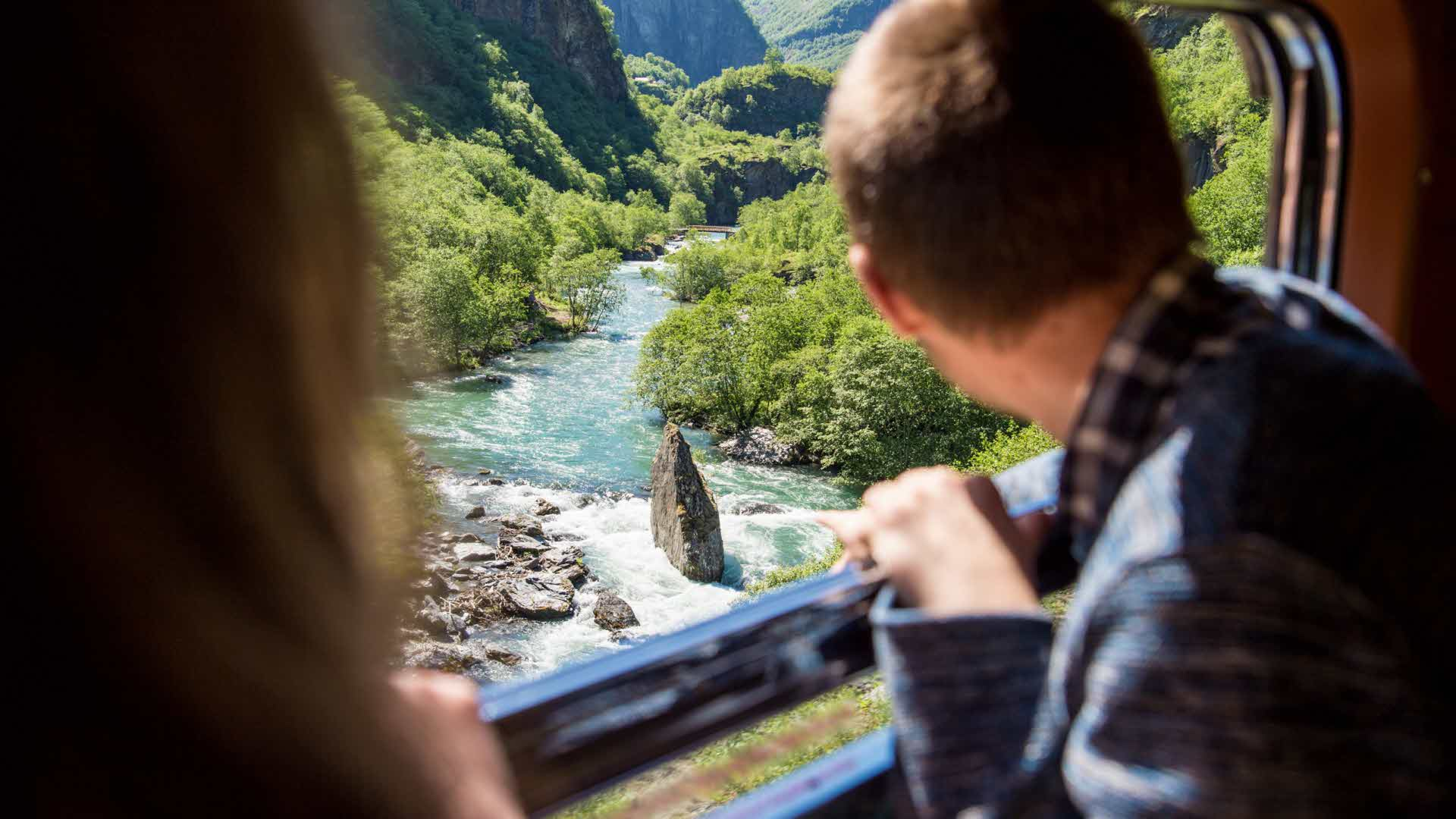 Couple looking at 'Vetleøya' rock in Flam river as passing with the Flam railway