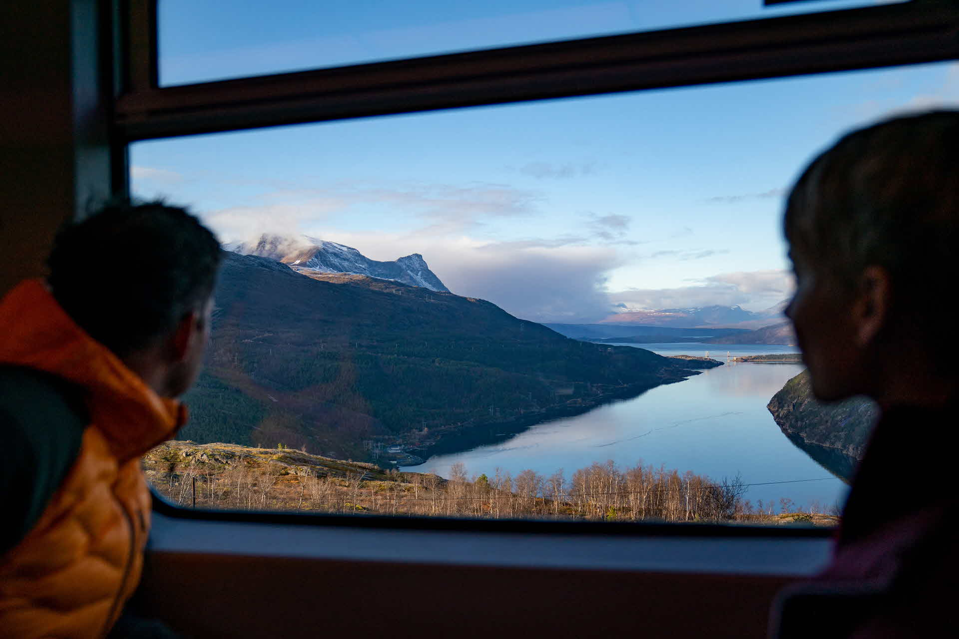 Young couple in looking out the coach window on The Arctic Train as passing viewpoint overlooking the Rombakfjord