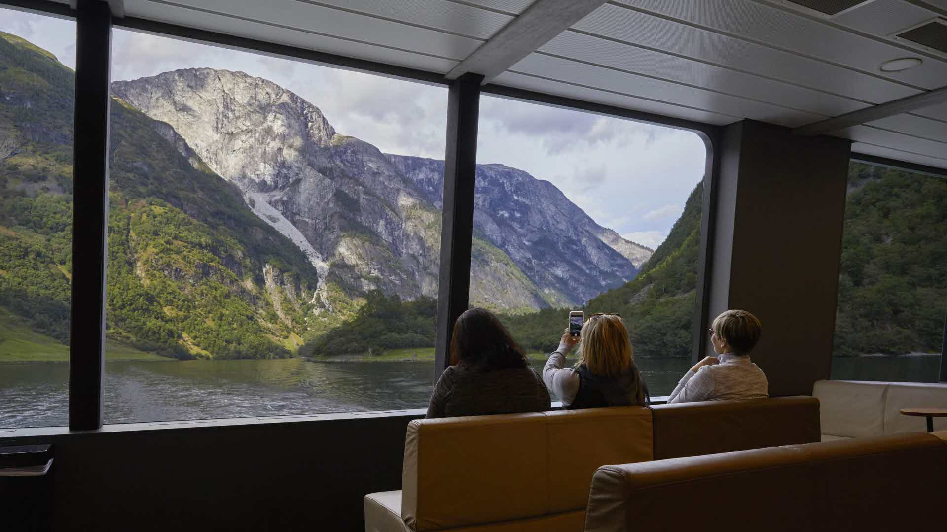 3 girlfriends takes pictures of scenery in Naeroyfjord through the big panorama windows on board Future of The Fjords