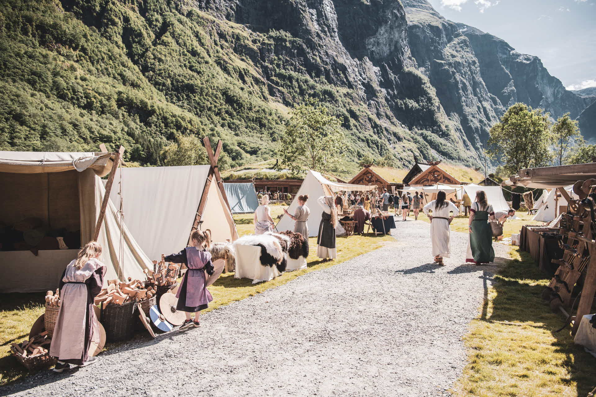 Children and adults in Viking clothes standing next to authentic tents in Gudvangen