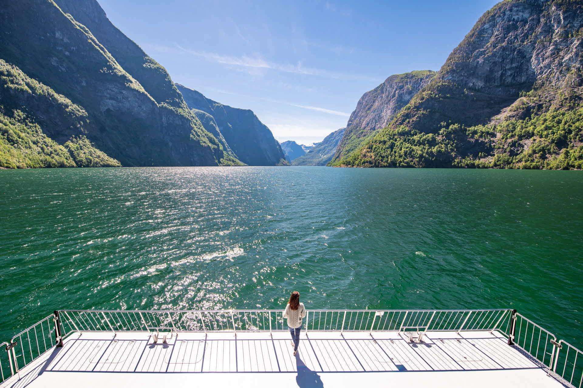 A woman stands at the bow of the Future of the Fjords, looking in towards the Nærøyfjord