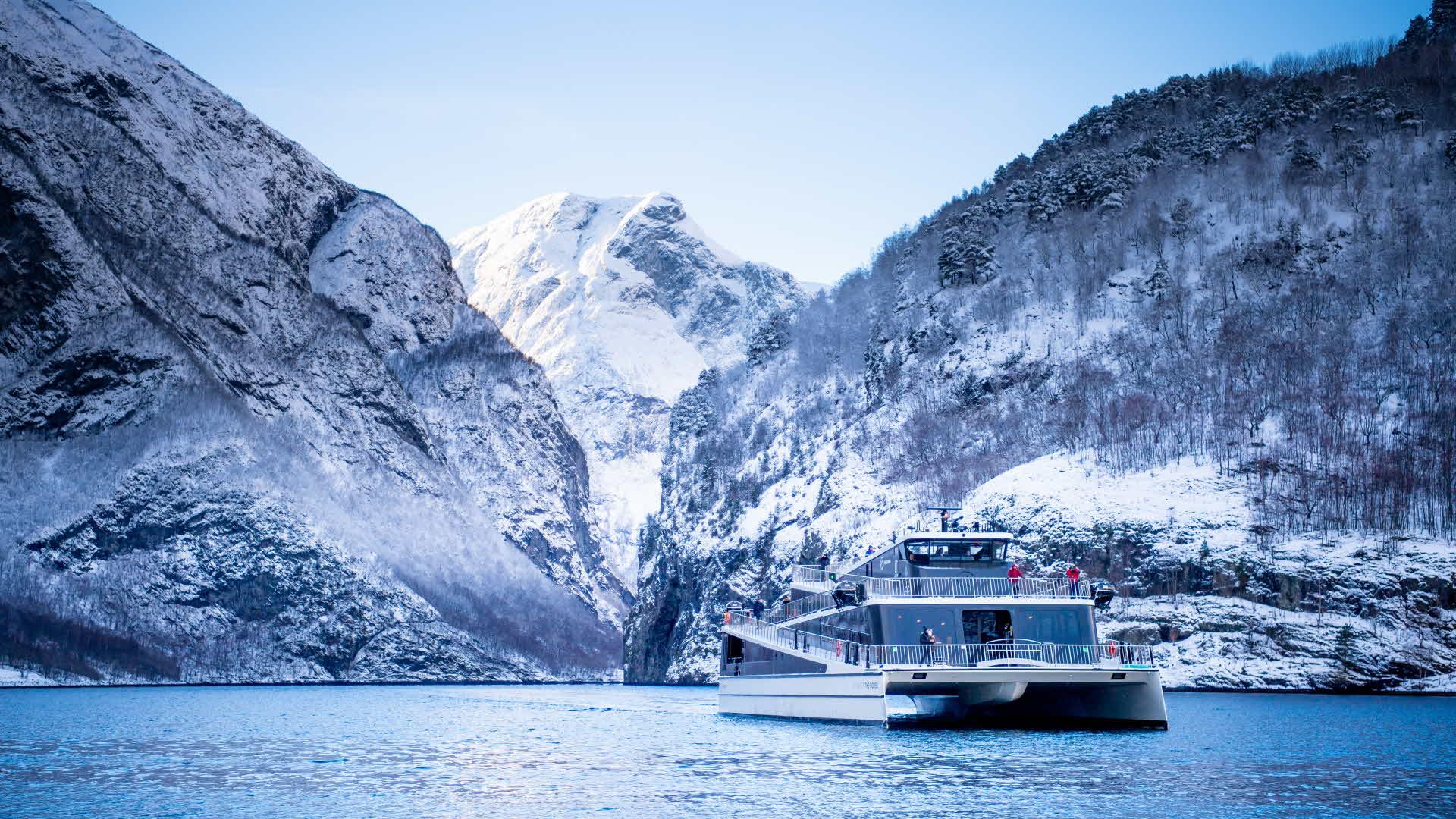 Elbåten Future of The Fjords foran snødekte fjell i Nærøyfjorden