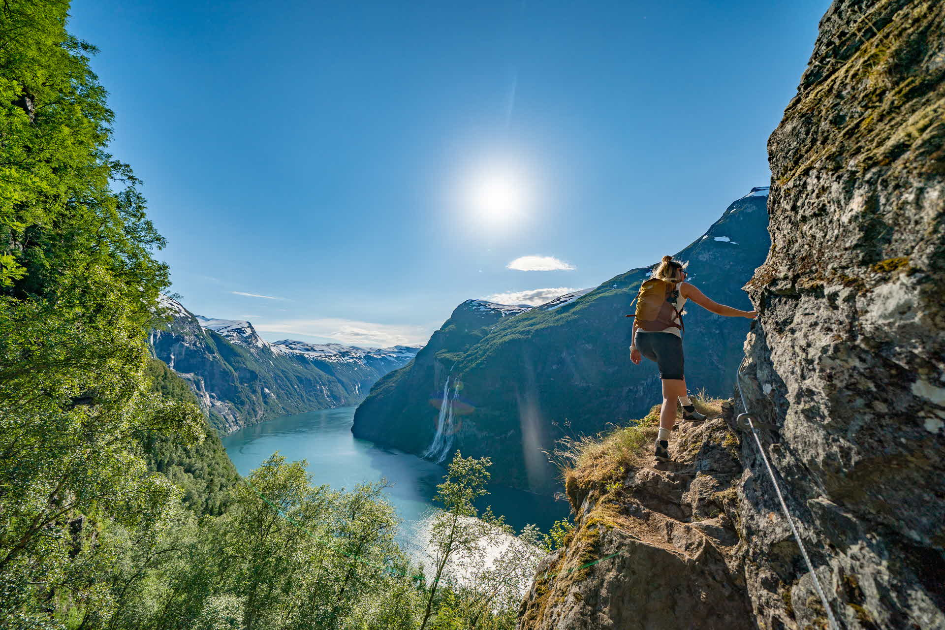 A woman hiking on a cliff with views to Geirangerfjord and waterfalls
