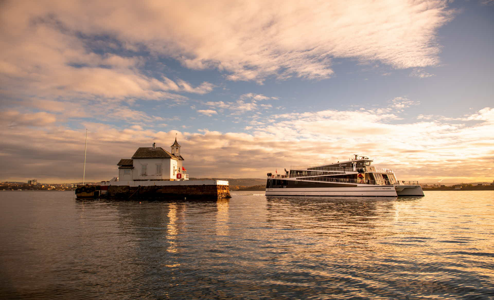 The hybrid vessel Vision of The Fjords next to a light house on a very small island in the Oslofjord in calm sea and sunset