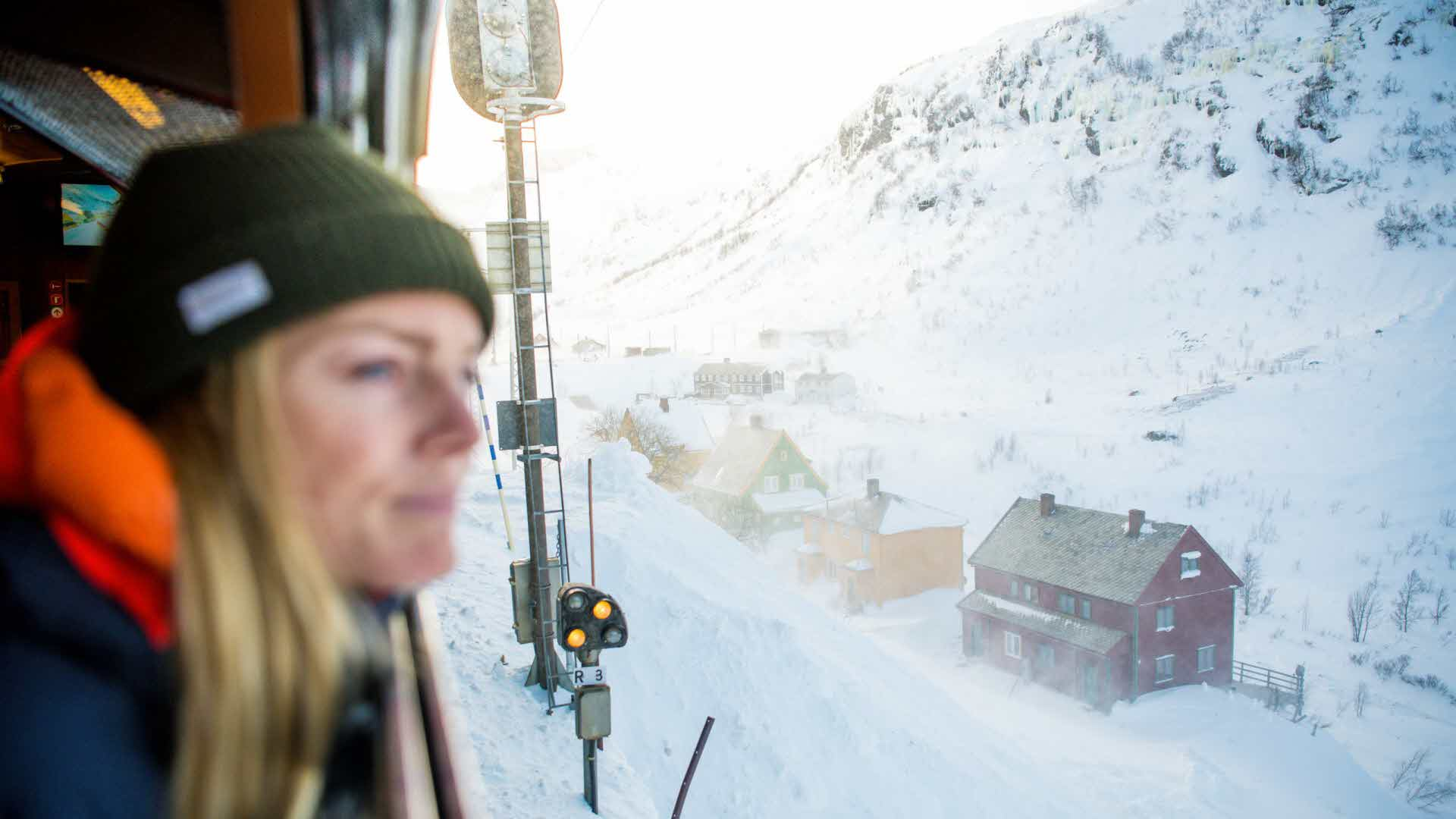 Woman looking out the window from the Flåm Railway at the houses and snow on a sunny winters day at Myrdal