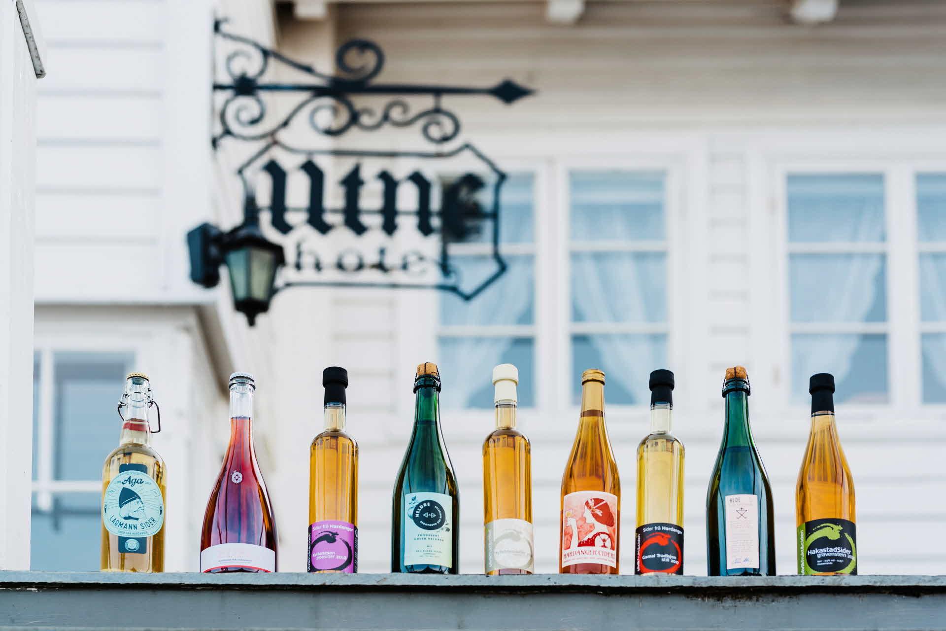Neun unterschiedlich geformte Ciderflaschen nebeneinander auf dem Geländer vor dem Utne Hotel in Hardanger, Norwegen