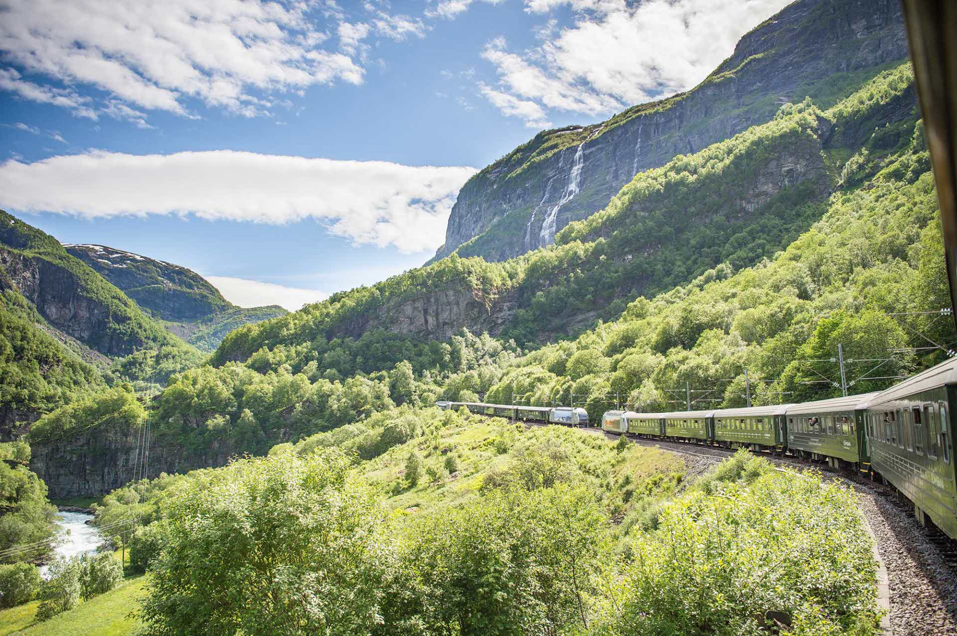 The Flam Railway trains passing each other in lush Flam valley with huge waterfall in the background and flowing river