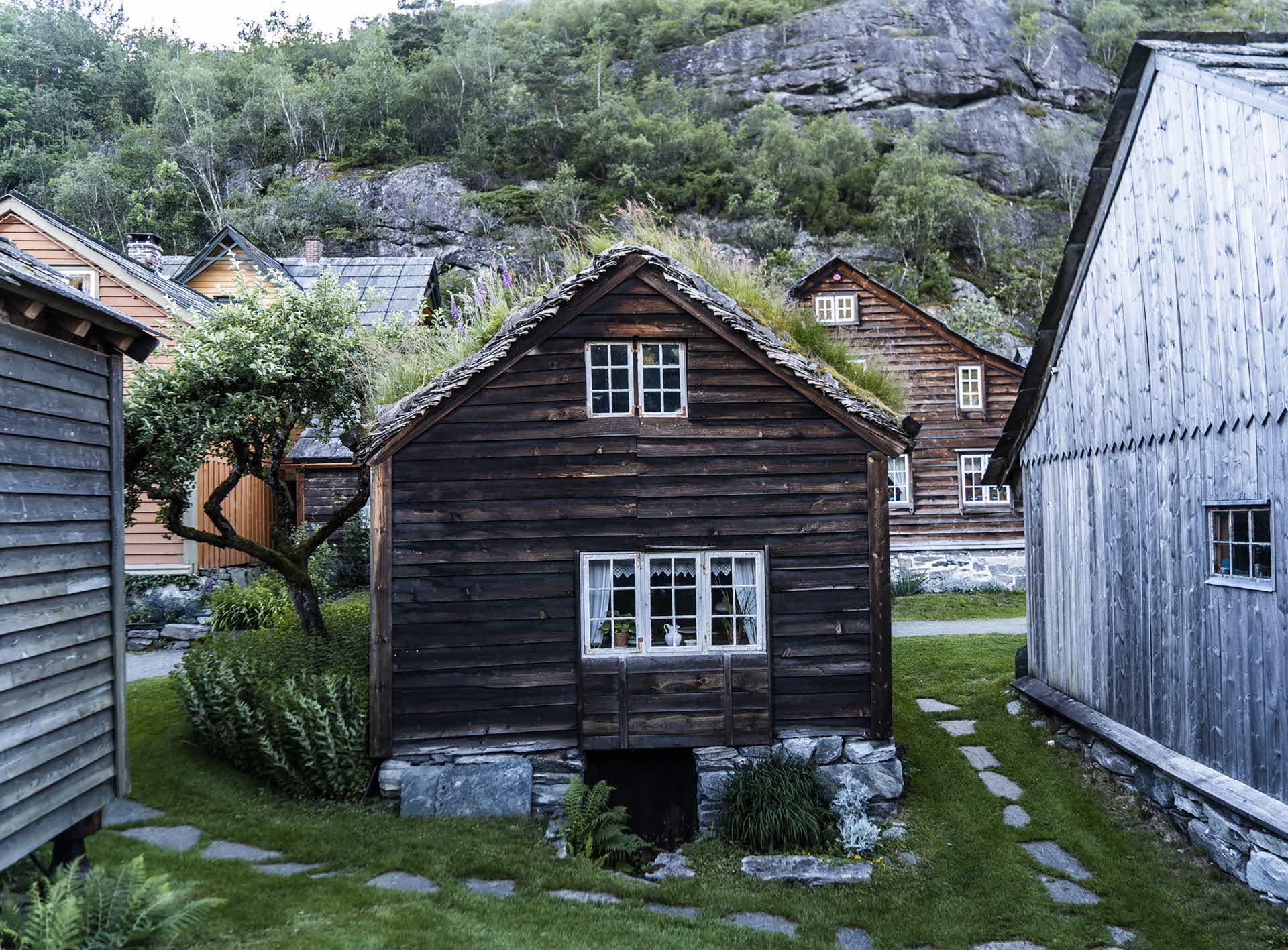 Ein kleines braunes Holzhaus aus den frühen 1220er Jahren, auf Natursteinen ruhend und mit Gras auf dem Dach, auf Agatunet in Hardanger, Norwegen