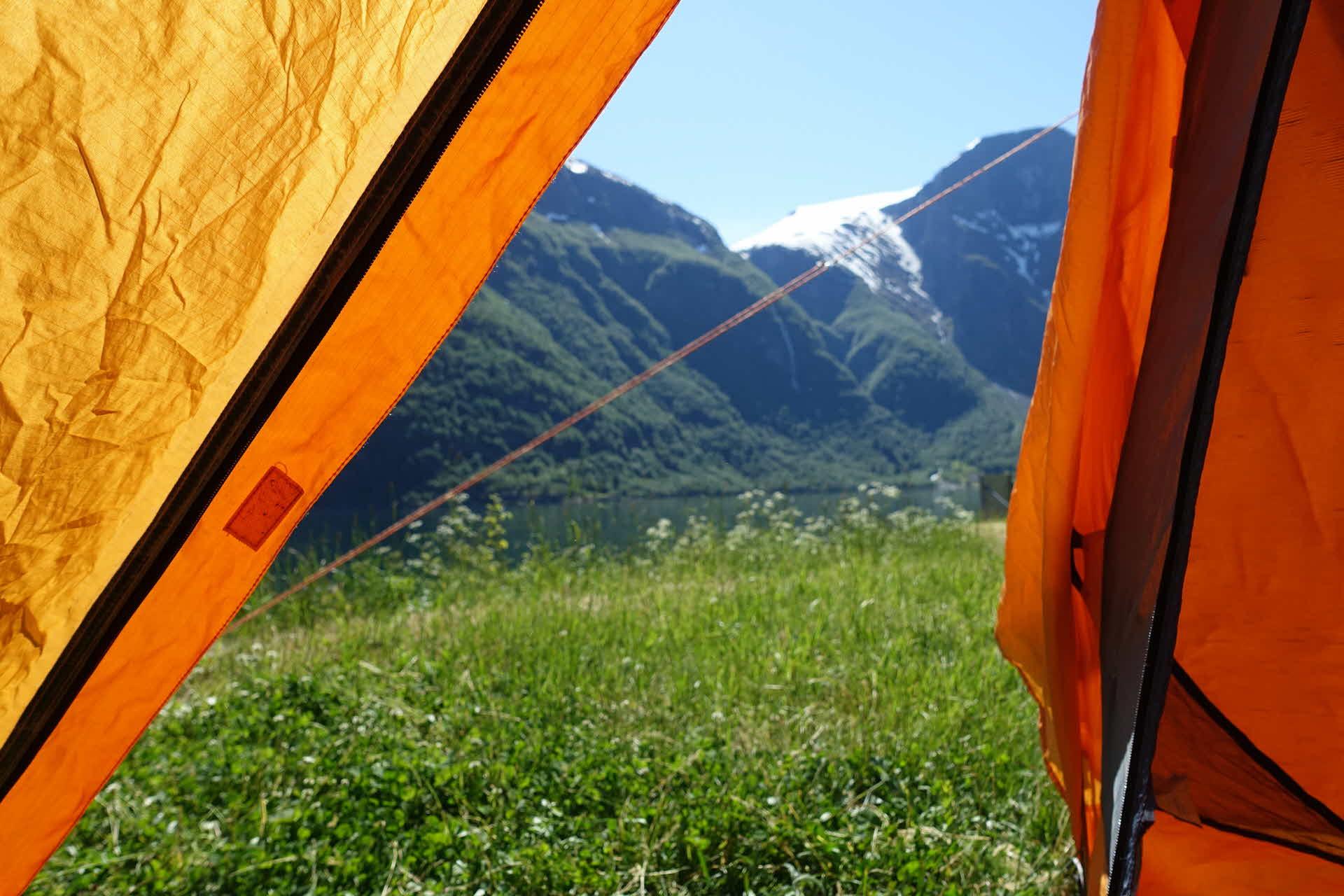 Utsikt gjennom oransje teltåpning med grønn eng i front og høye fjell i bakgrunnen med snøkledte topper