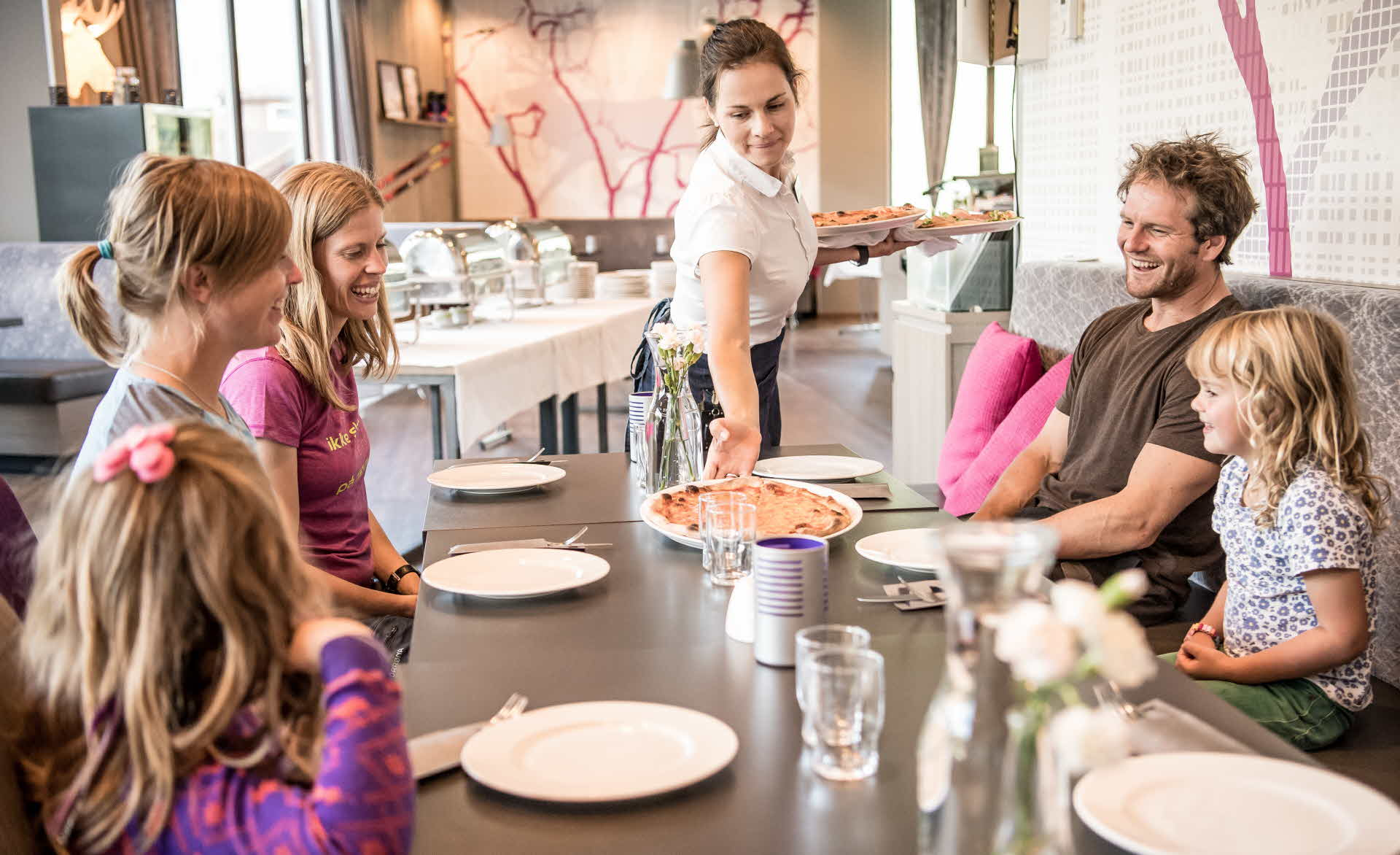 Happy family of five being served pizza as dining at Myrkdal Ski Resort Restaurant