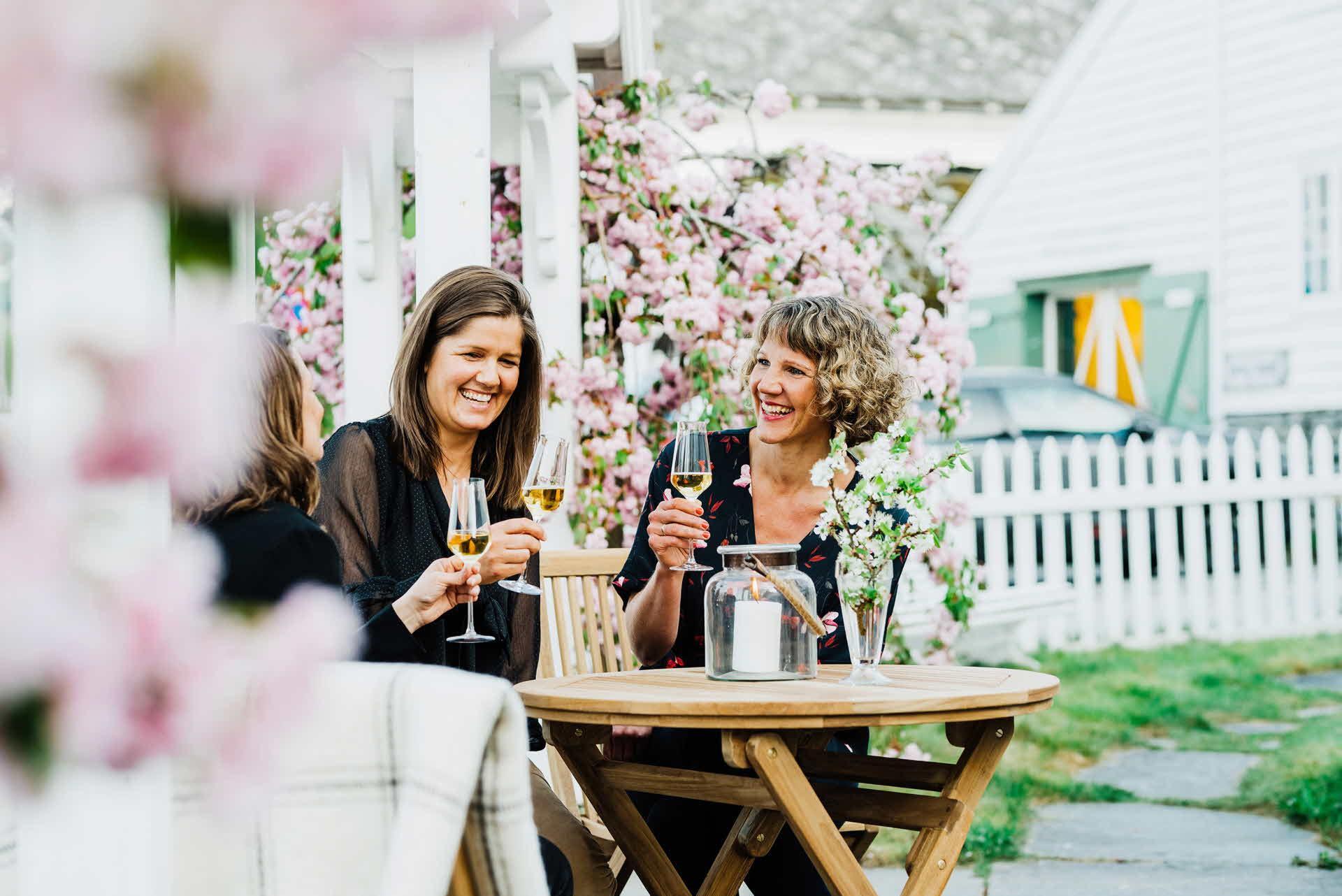 3 blide damer i 40 årene koser seg og drikker sider i en blomsterhage i Hardanger