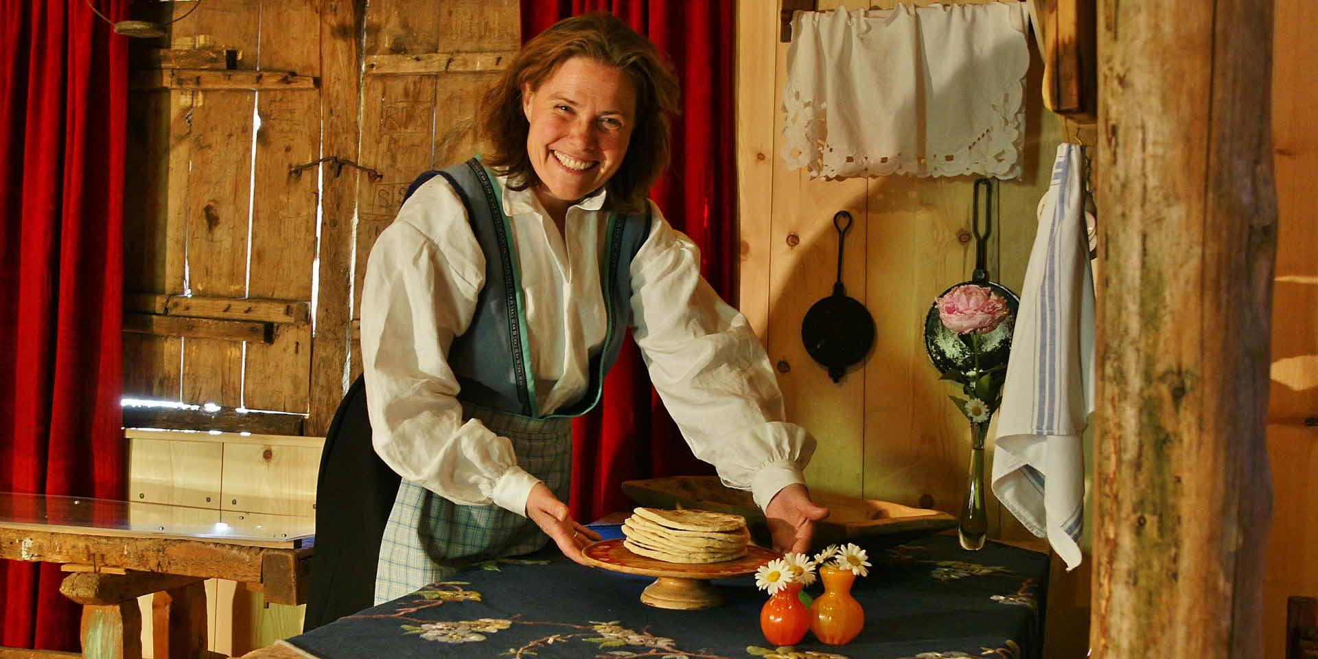 美しい民族衣装を着た女性が、伝統的なキッチンで微笑みながら地元産のフラットブレッドを手渡します。