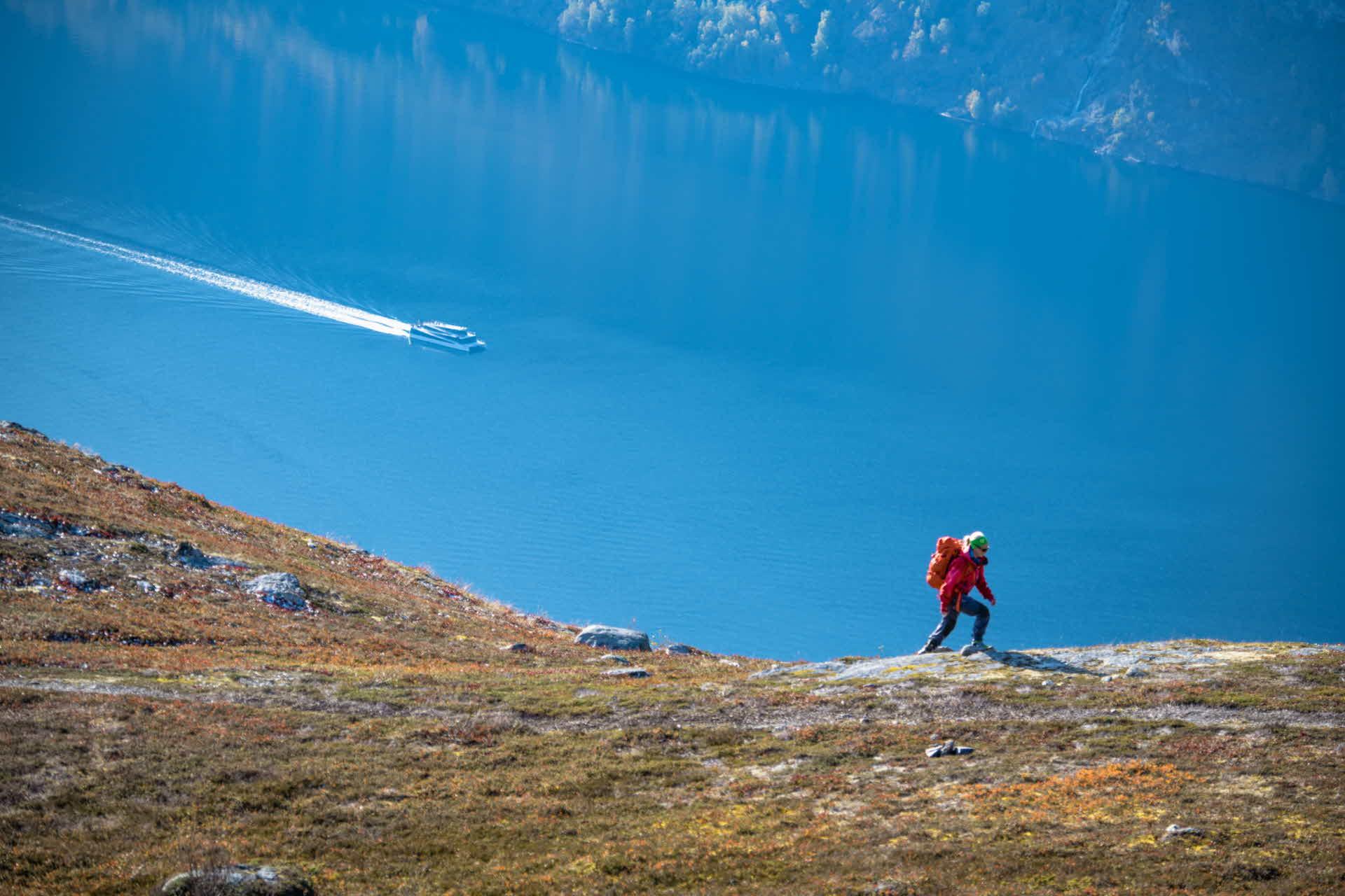 Kvinne går på sti oppover mot Prest med båt seglende på fjorden under