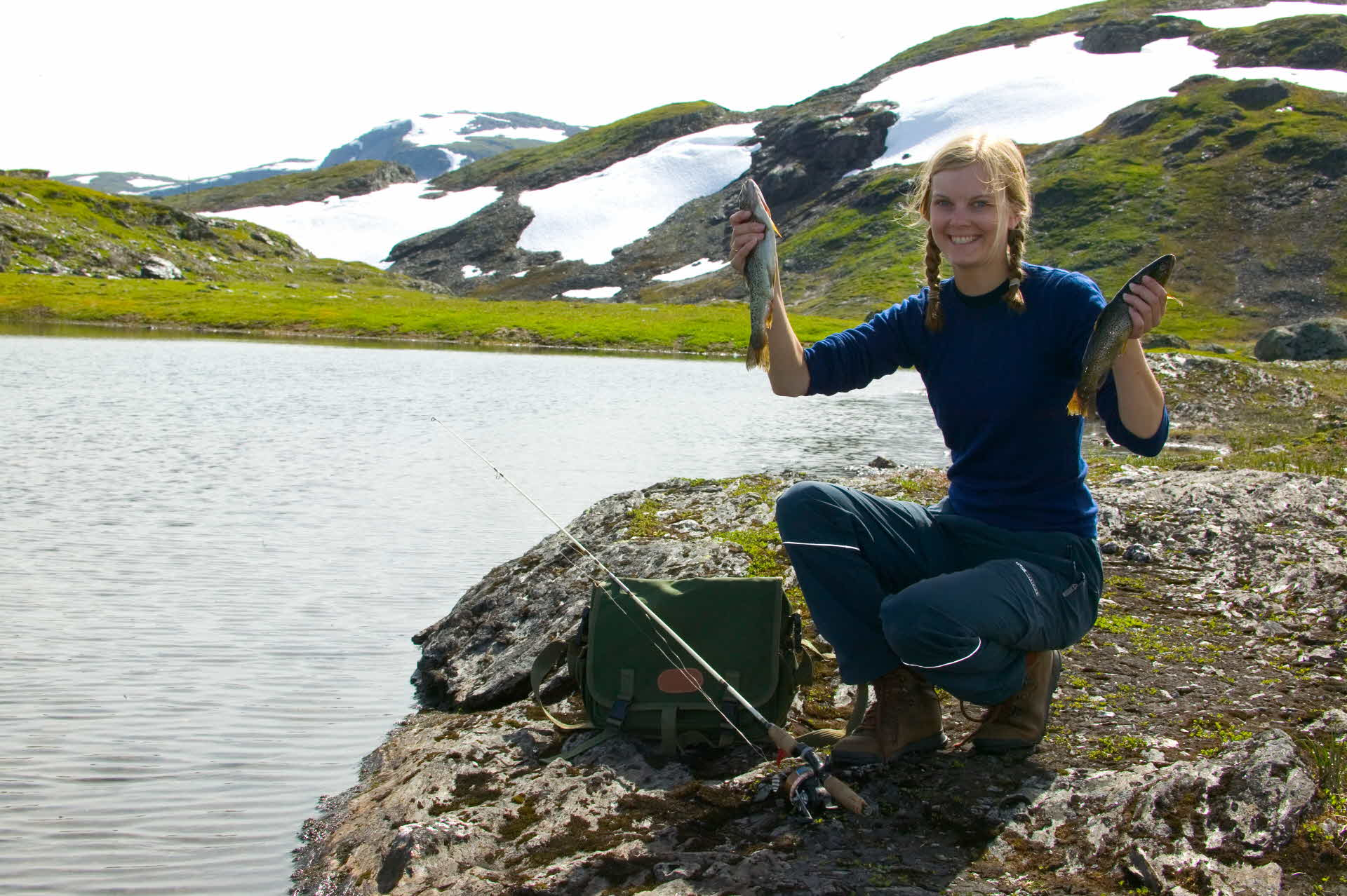 A girl holding up two fish beside a mountain lake