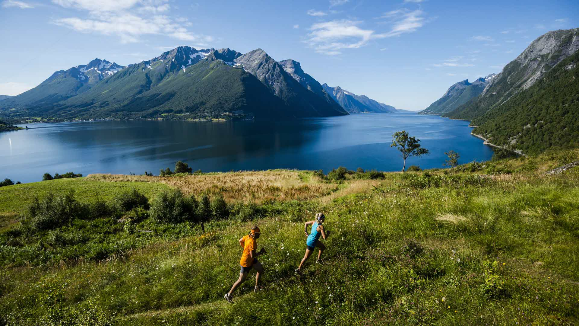 2 people in summer jogging by the hjorondfjord dramatic mountains in background