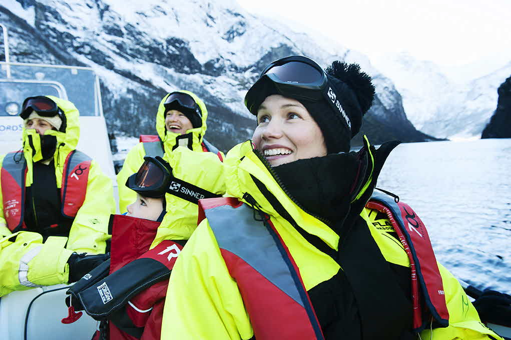 4 people in full flotation body suits in a RIB boat on UNESCO-listed Naeroyfjord surrounded by snowy mountains