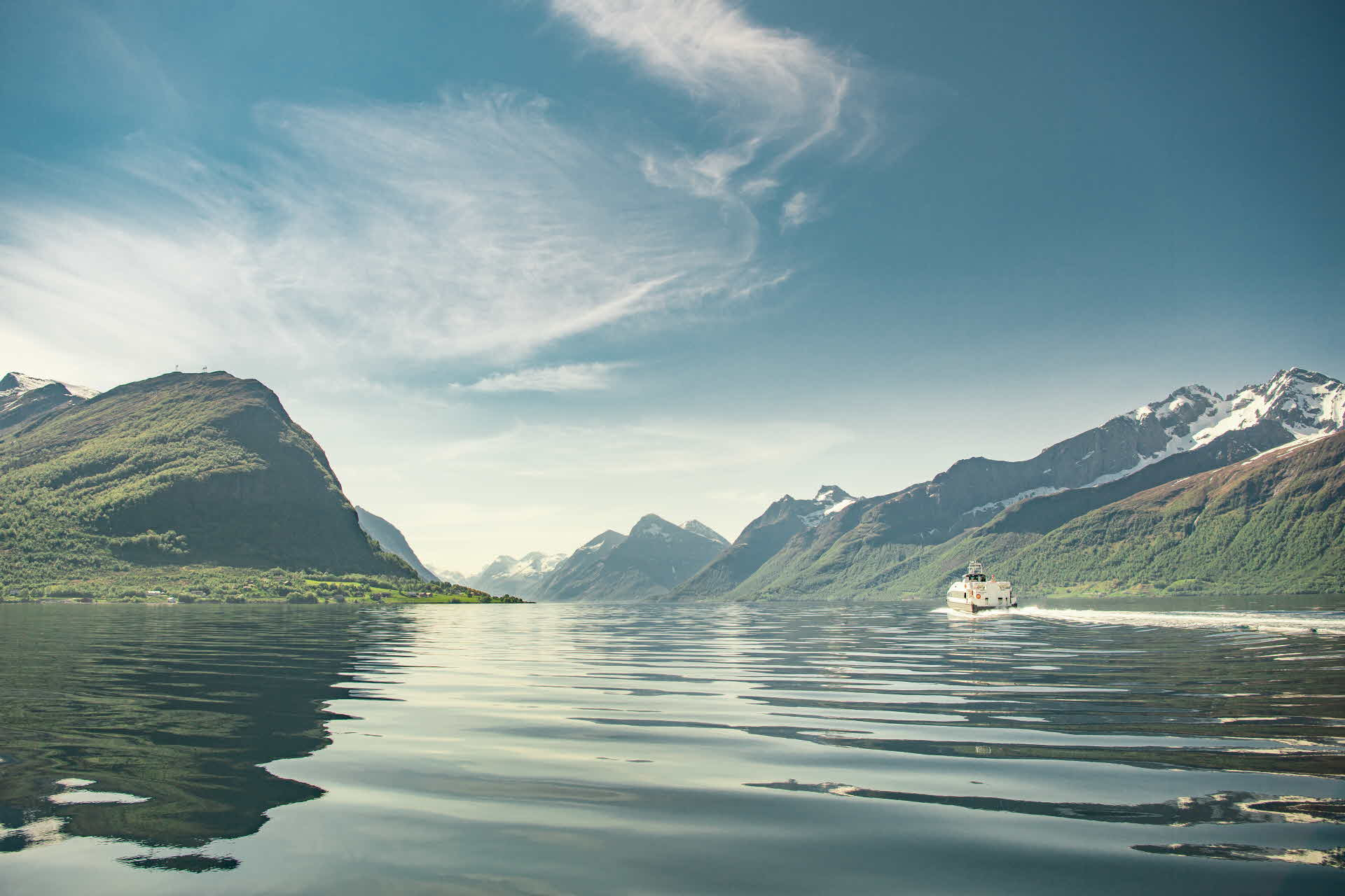 A boat sailing towards the Sunnmørsalpene range in fine weather