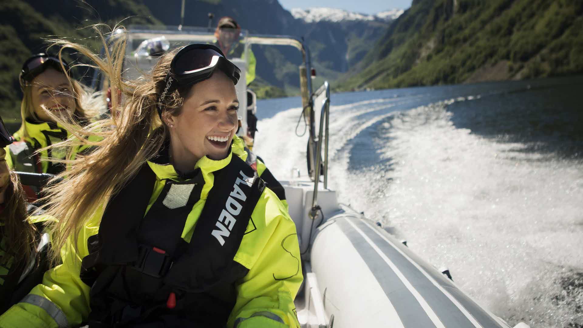 En glad kvinne med vind i håret om bord i en rib i full fart på Nærøyfjorden en solrik dag