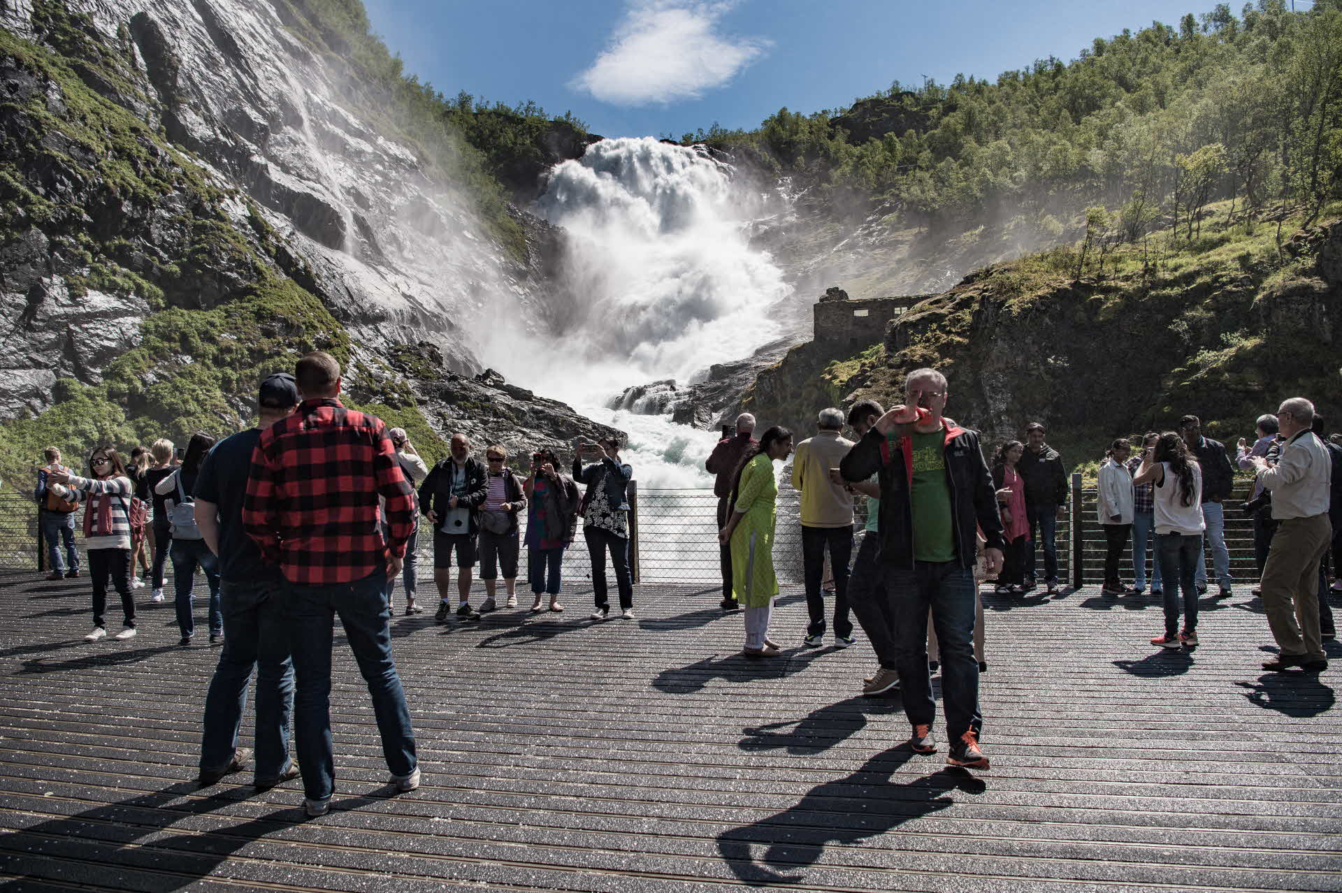 Group of tourists in summer standing on the Flam Railway viewing platform overlooking the thundering Kjosfossen waterfall