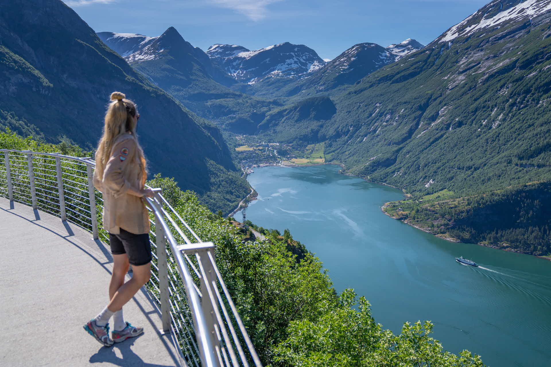 A woman standing on Ørnesvingen view platform above the Geirangerfjord