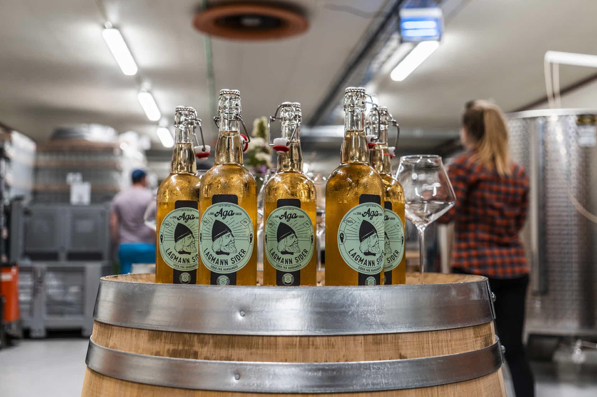 6Aga-Ciderflaschen auf einem Holzfass im Inneren der Aga-Ciderbrauerei in Hardanger