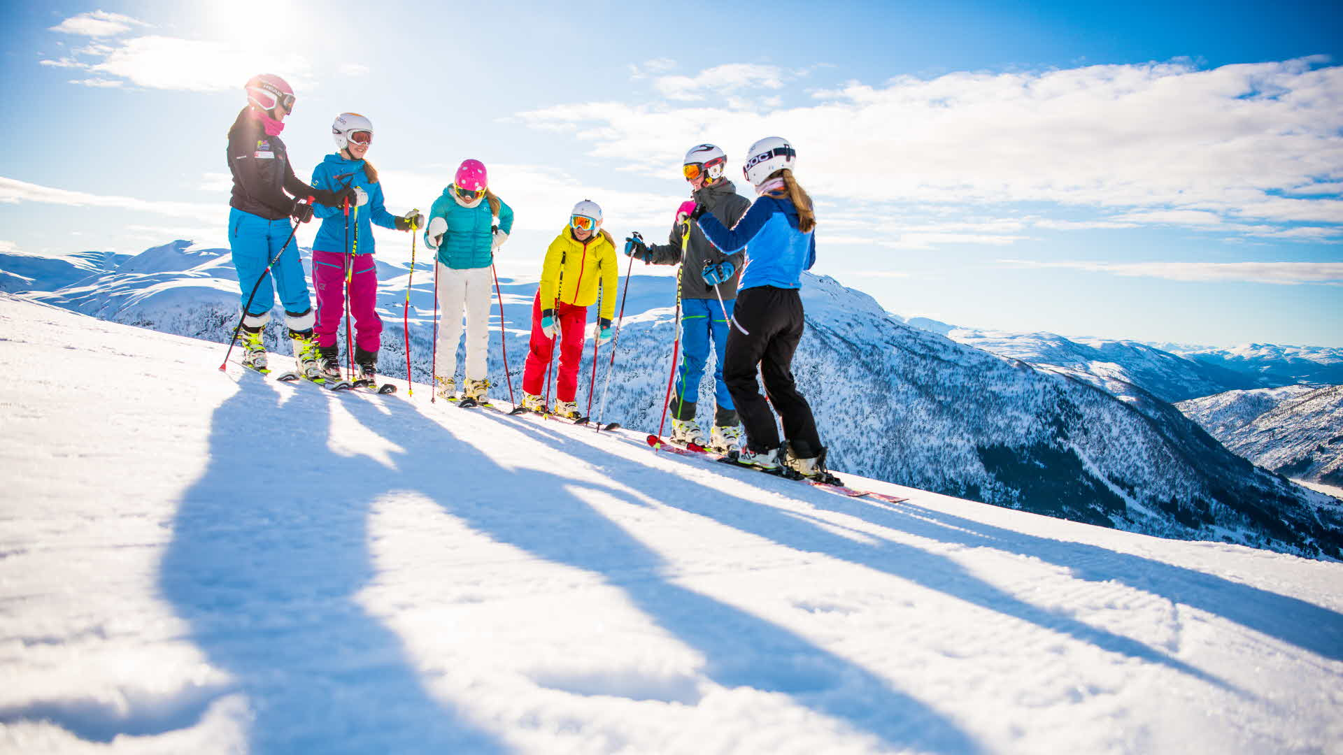 6 people in alpine downhill gear standing at Myrkdalen Ski Resort ski slopes on crisp sunny day overlooking the winter landscape