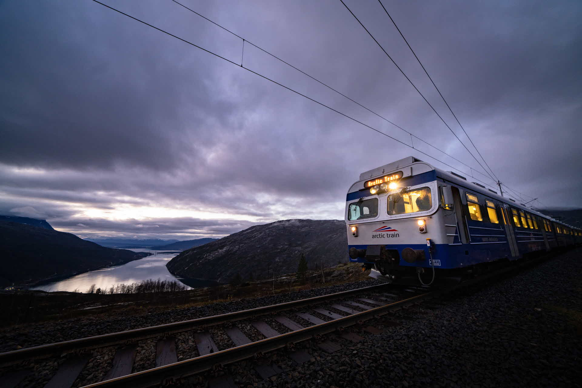 Lights from The Arctric Train on the Ofot railway illuminate when stop at top of mountain late evening by  Rombakfjord